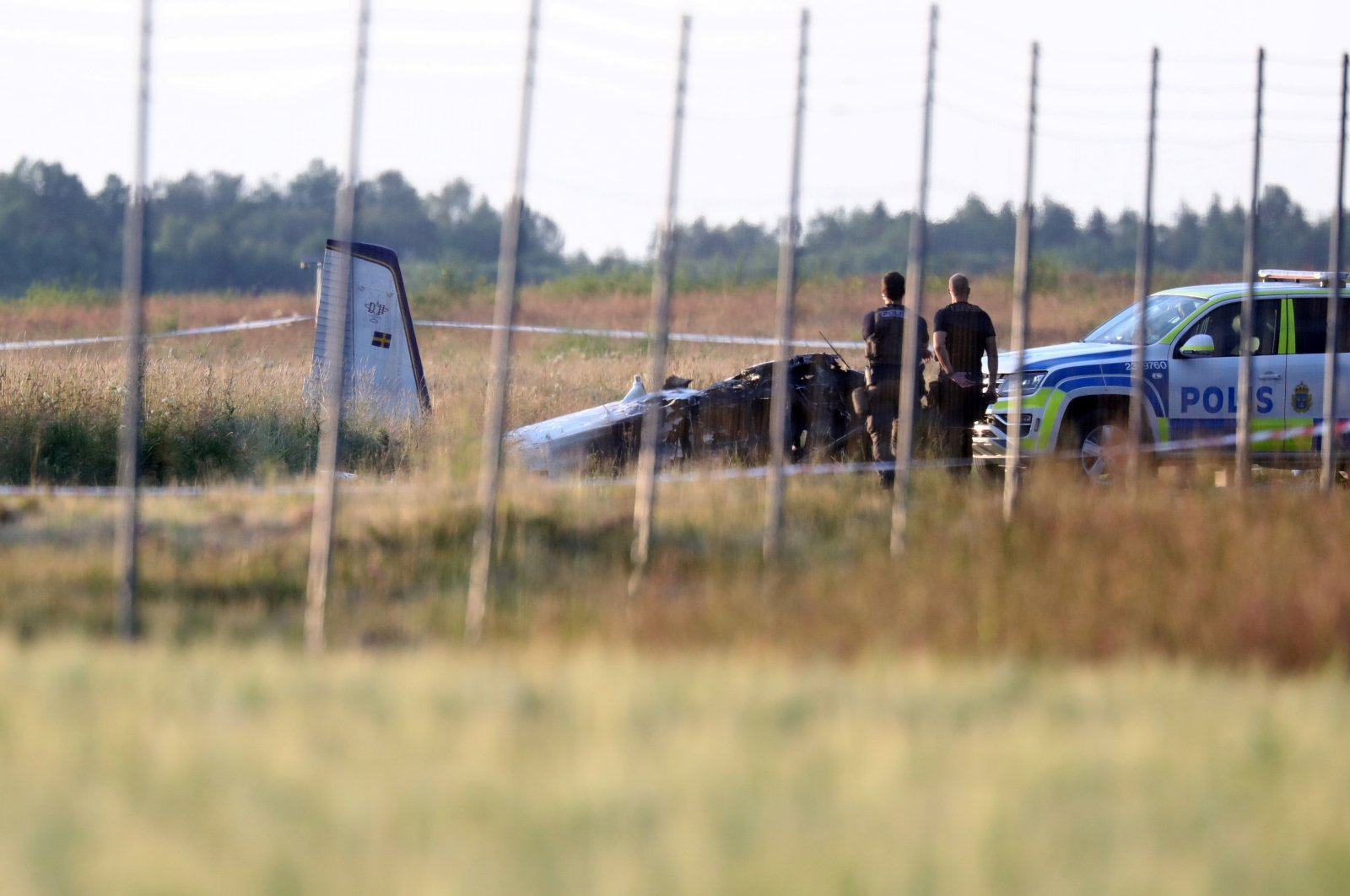 Police officers investigate the site where a small aircraft crashed at Orebro Airport, Orebro, Sweden, July 8, 2021. (Reuters Photo)