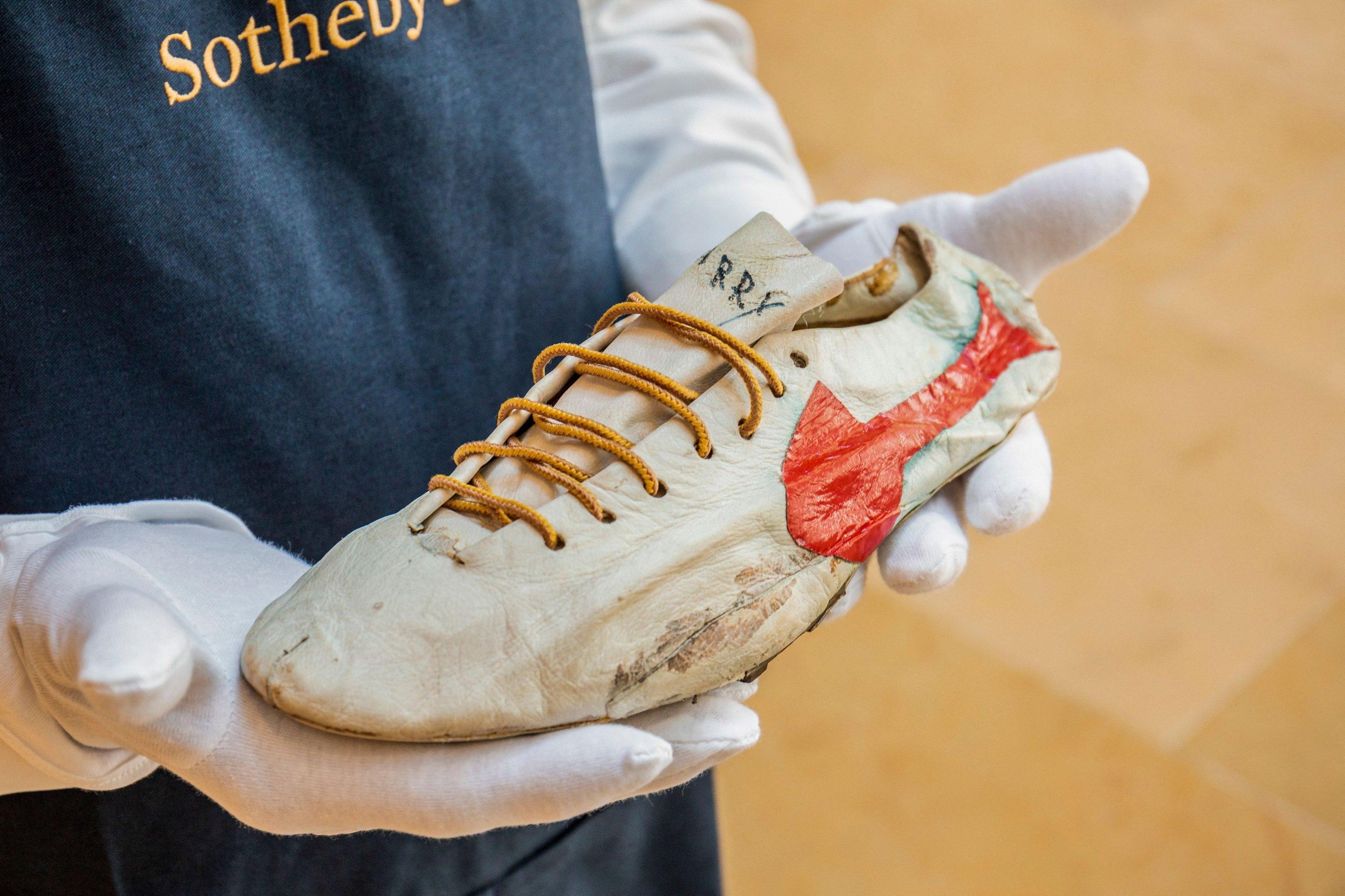 A Sotheby's staff holds a 'prototype logo' track spikes running shoe handmade by Nike co-founder Bill Bowerman in the 1960s, New York, U.S., July 7, 2021. (Sotheby's/AFP Photo)