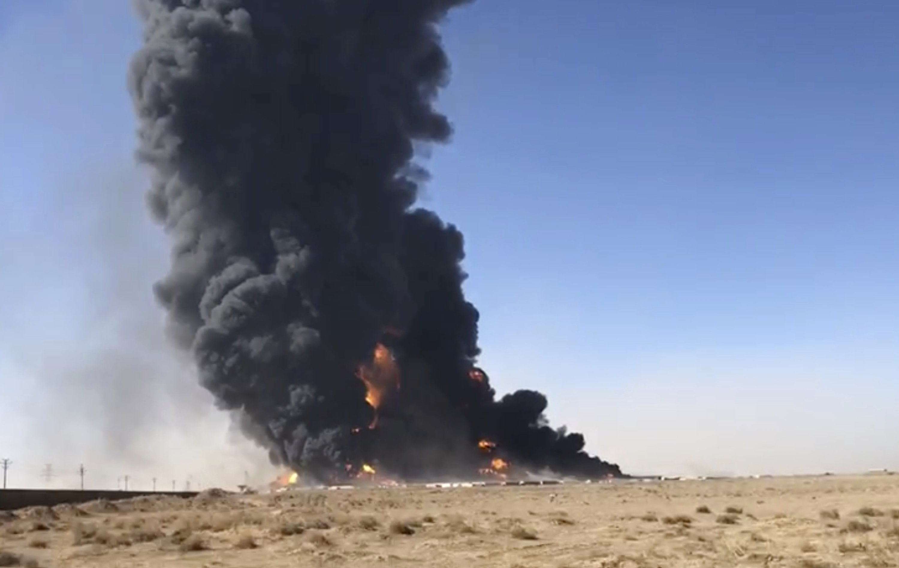 Smoke rises from fuel tankers at the Islam Qala border with Iran, in Herat Province, west of Kabul, Afghanistan, Feb. 13, 2021. (AP Photo)