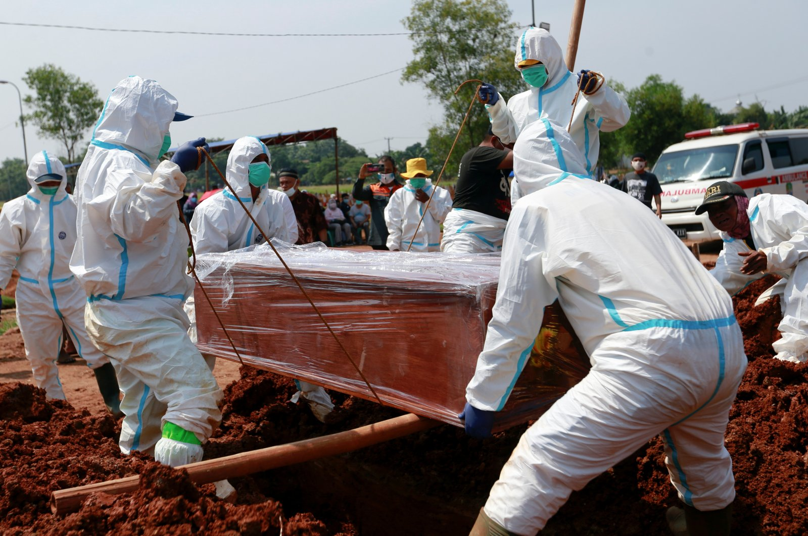 Gravediggers wearing personal protective equipment (PPE) bury a coffin at a Muslim burial area provided by the government for coronavirus victims in Bekasi, on the outskirts of Jakarta, Indonesia, July 8, 2021. (Reuters Photo)