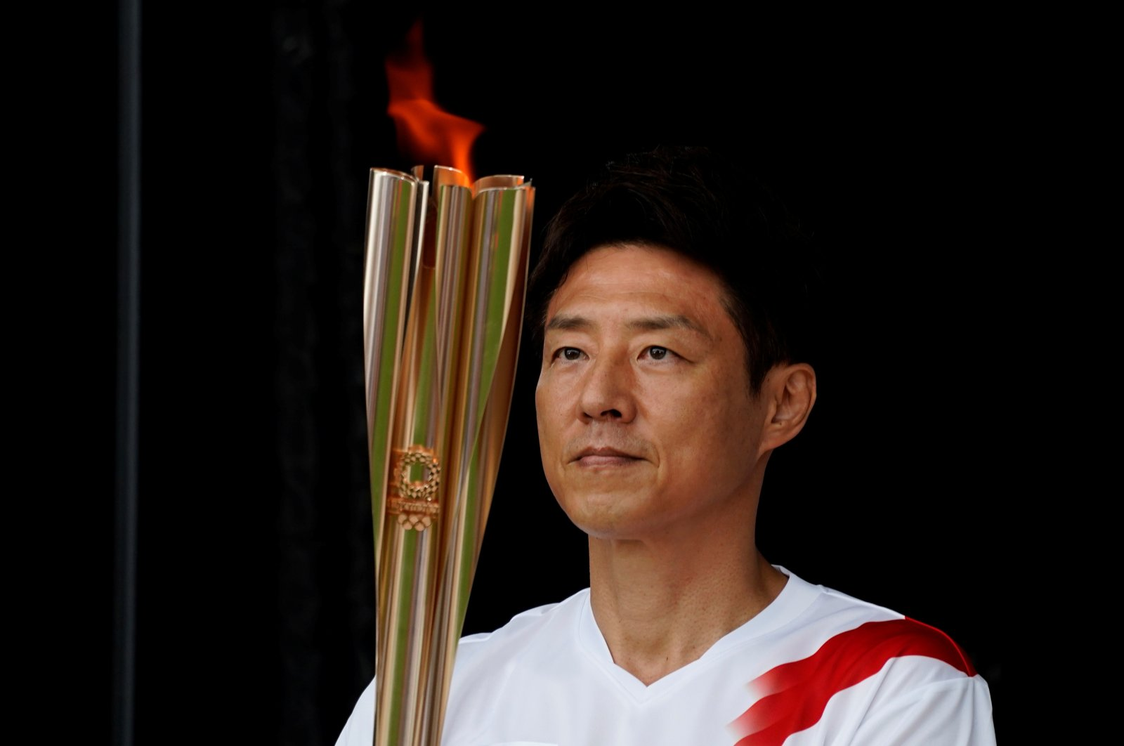 Shuzo Matsuoka, Tokyo's first torchbearer, holds the torch at a lighting ceremony during which torchbearers pass the flame to the next one via a torch kiss, after their relay on a public road was canceled due to the coronavirus pandemic, at the Tokyo 2020 Olympic torch relay celebration in Tokyo, Japan, July 9, 2021. (Reuters Photo)