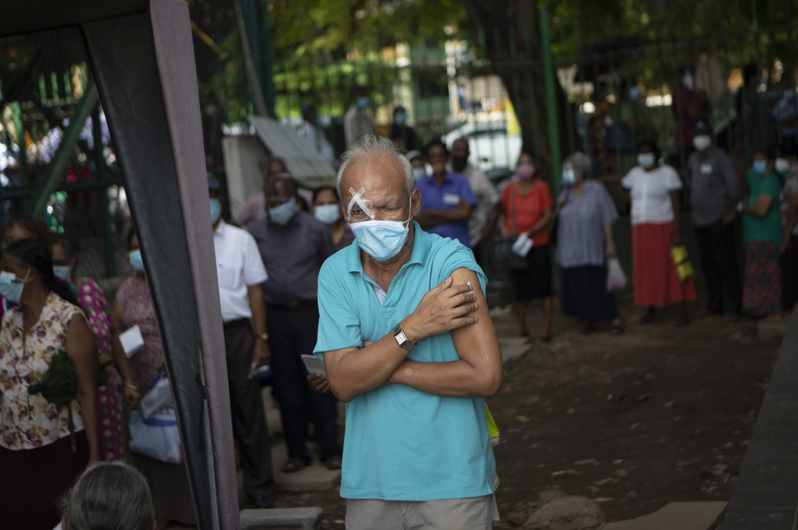 An elderly Sri Lankan holds his arm after receiving a dose of Pfizer COVID-19 vaccine at a vaccination site in Colombo, Sri Lanka, Wednesday, July 7, 2021.  (AP Photo)