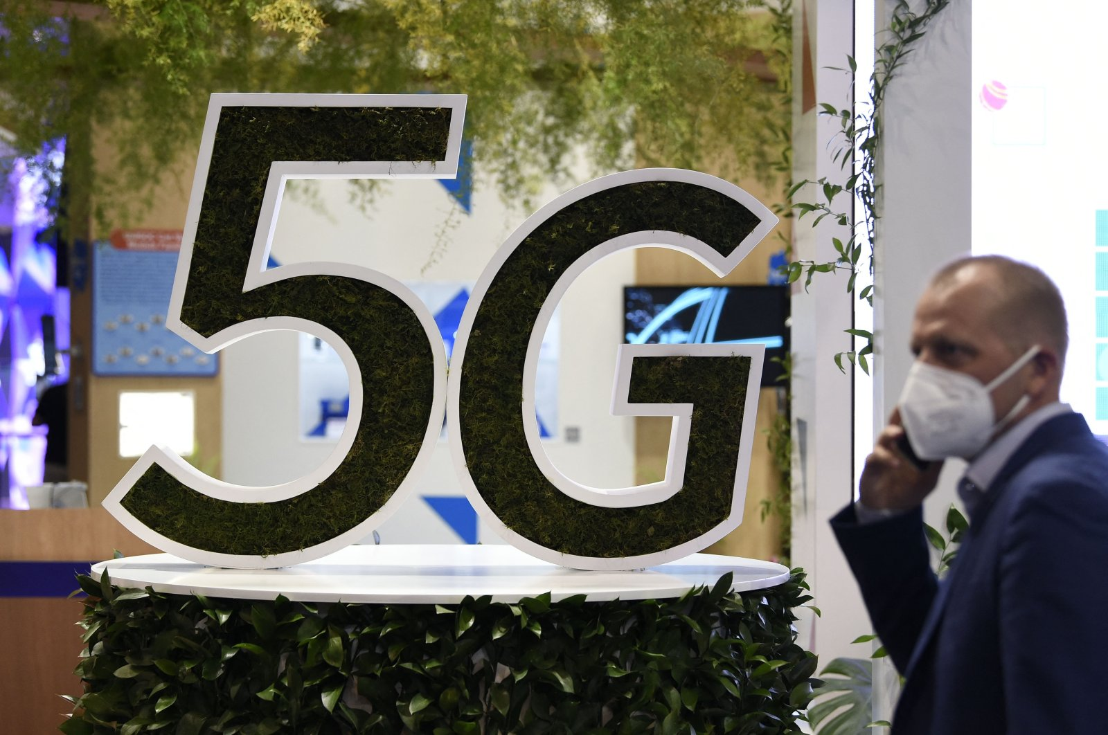 The man uses his mobile phone next to a 5G logo at the Mobile World Congress (MWC) fair in Barcelona, Spain, June 29, 2021. (AFP Photo)