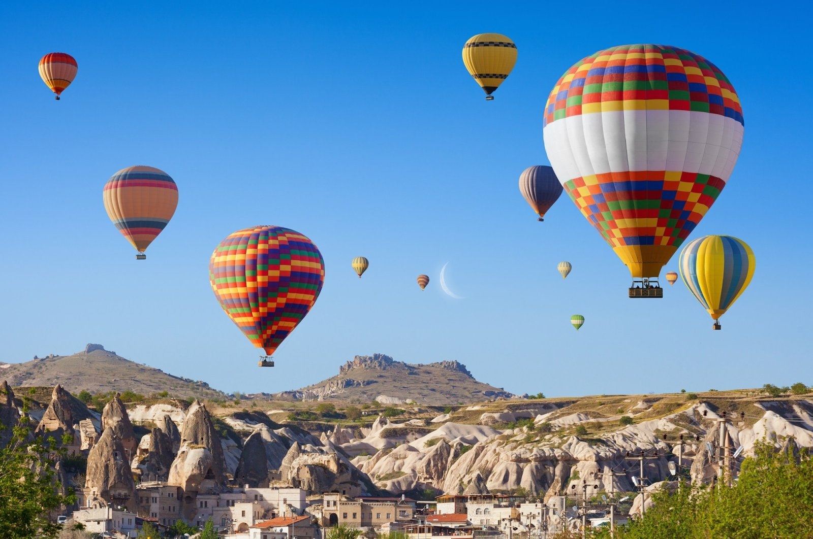 Colorful hot air balloons fly above the road to Göreme at sunrise in Cappadocia, Turkey. (Shutterstock Photo)