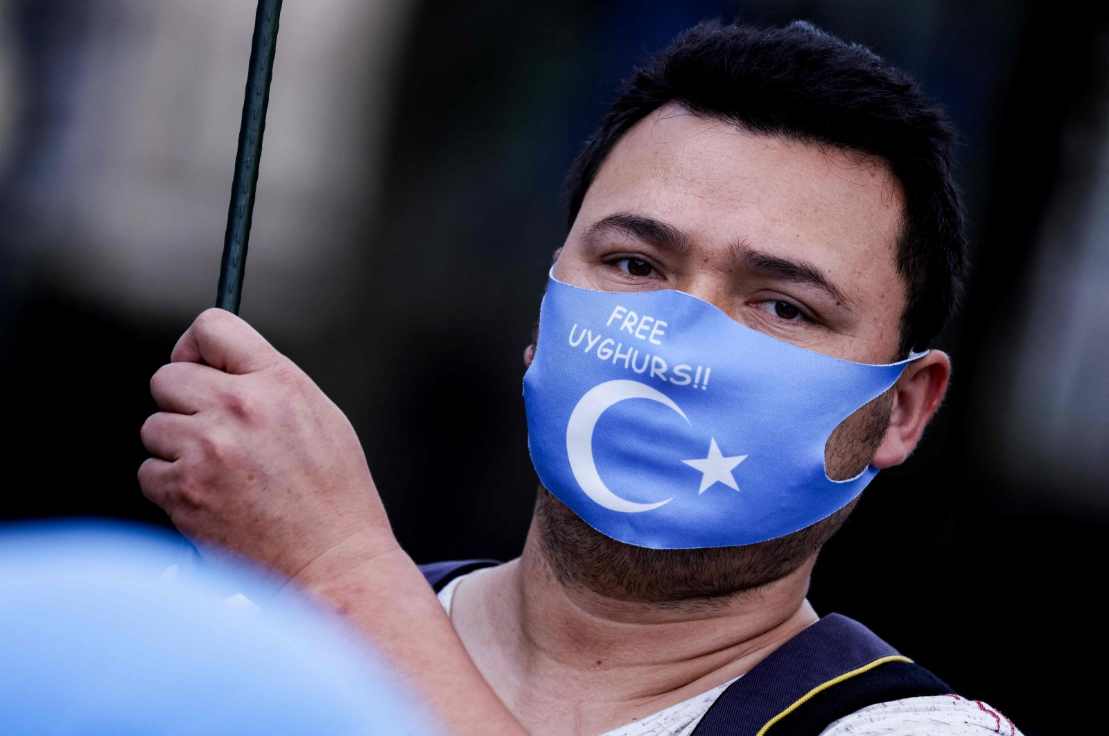 """A demonstrator from the Uyghur Community waves a flag during a protest near the Belgium parliament in Brussels, the day Belgian MPs are due to vote a resolution denouncing """"serious risk of genocide"""" against China's Uyghurs. July 8, 2021. (AFP Photo)"""