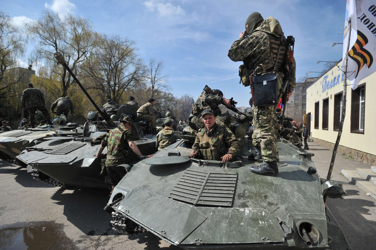 Armed men wearing military fatigues gather by Armoured Personnel Carriers (APC) as they stand guard outside the regional state building seized by pro-Russian separatists in the eastern Ukrainian city of Slavyansk on April 16, 2014. (AFP Photo)