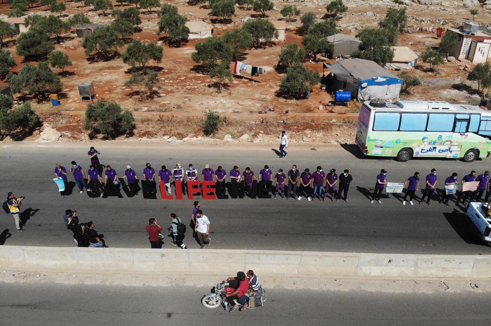 Activists and workers from civil society, humanitarian and medical aid organizations form a human chain calling on the international community to maintain the cross-border humanitarian corridor, at the Bab Al-Hawa border crossing, Idlib, Syria, July 2, 2021. (EPA Photo)