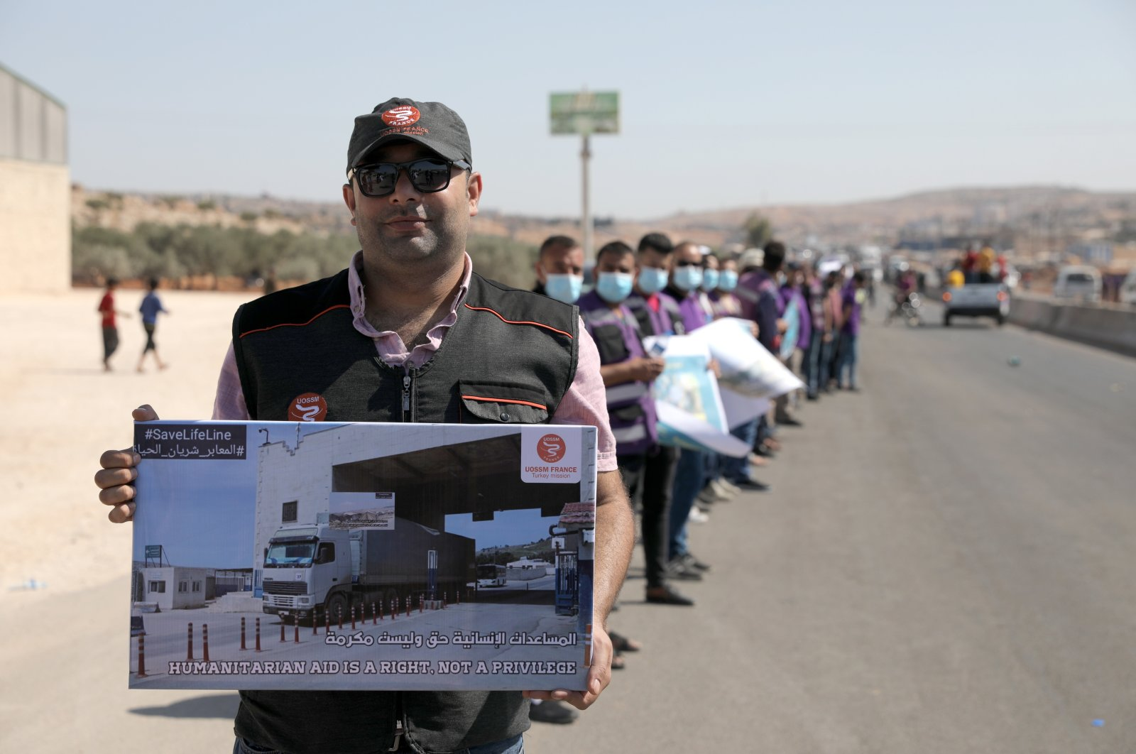 Activists and workers from civil society, humanitarian and medical aid organizations hold banners as they form a human chain calling on the international community to maintain the cross-border humanitarian corridor, at the Bab Al-Hawa border crossing, Idlib, Syria, July 2, 2021. (EPA Photo)