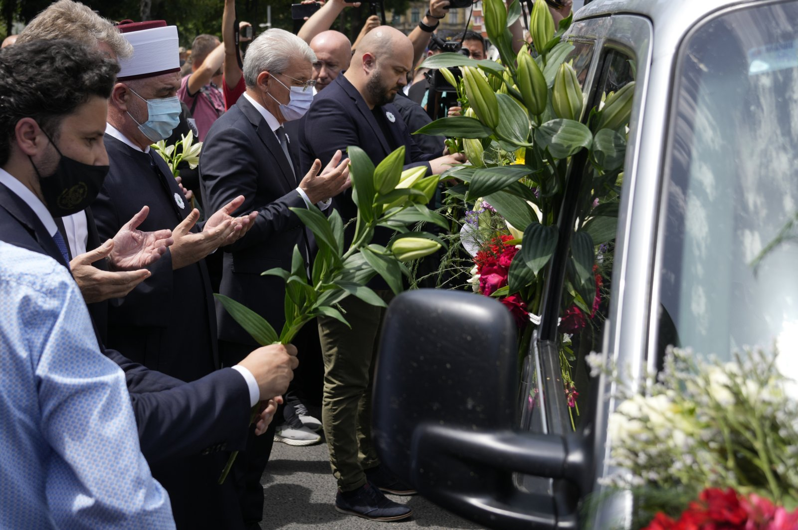 Dignitaries pay respect in front of a motorcade carrying 19 identified bodies of victims that will be buried in Srebrenica on Sunday, Sarajevo, Bosnia, July 9, 2021. (AP Photo)