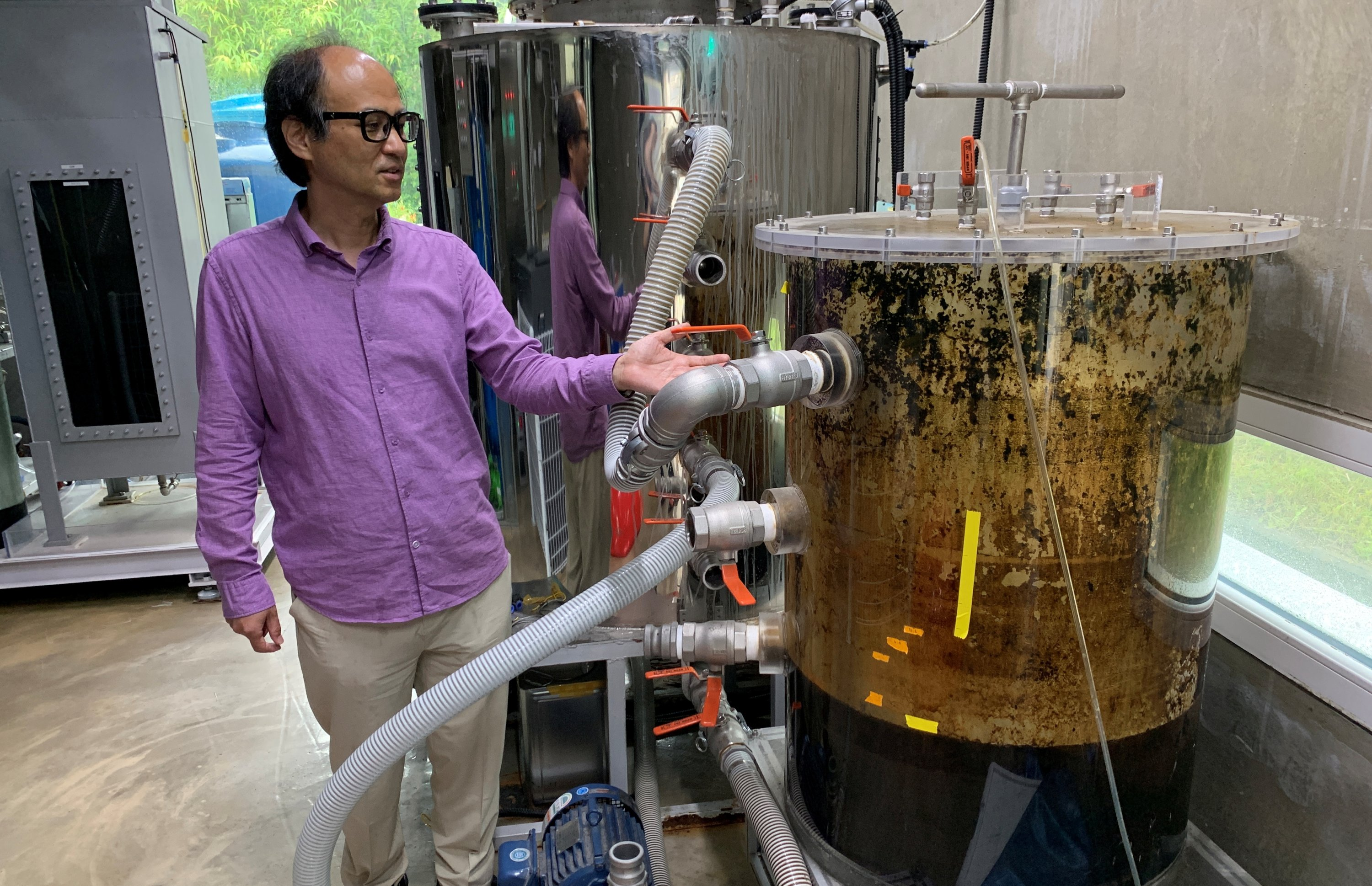 Cho Jae-weon, a South Korean professor at Ulsan National Institute of Science and Technology (UNIST), stands next to a feces tank at a laboratory in Ulsan, South Korea, July 6, 2021. (Reuters Photo)