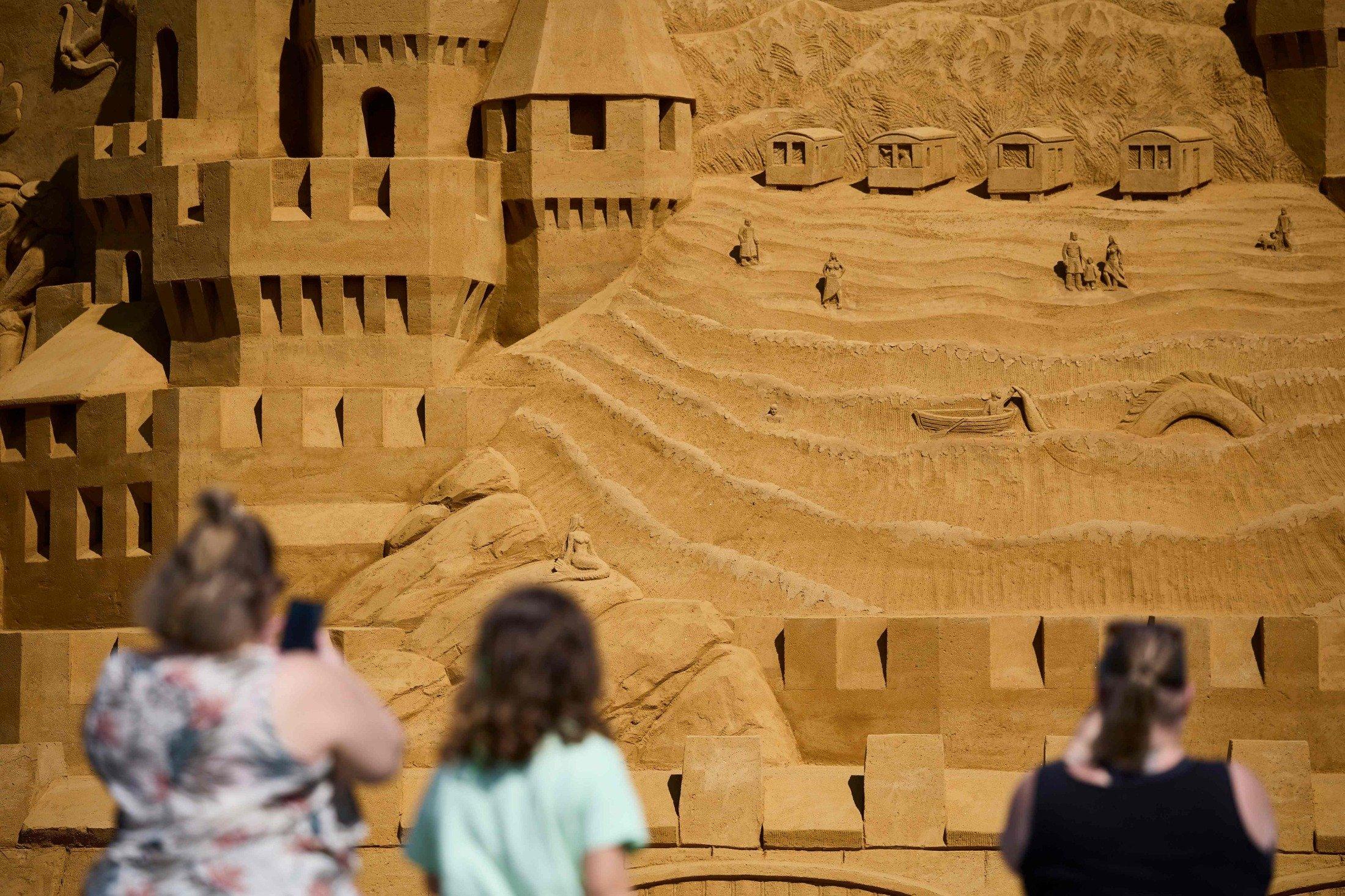 People visit the world's tallest sand sculpture, under construction in Blokhus, Denmark, July 7, 2021. (AFP Photo)