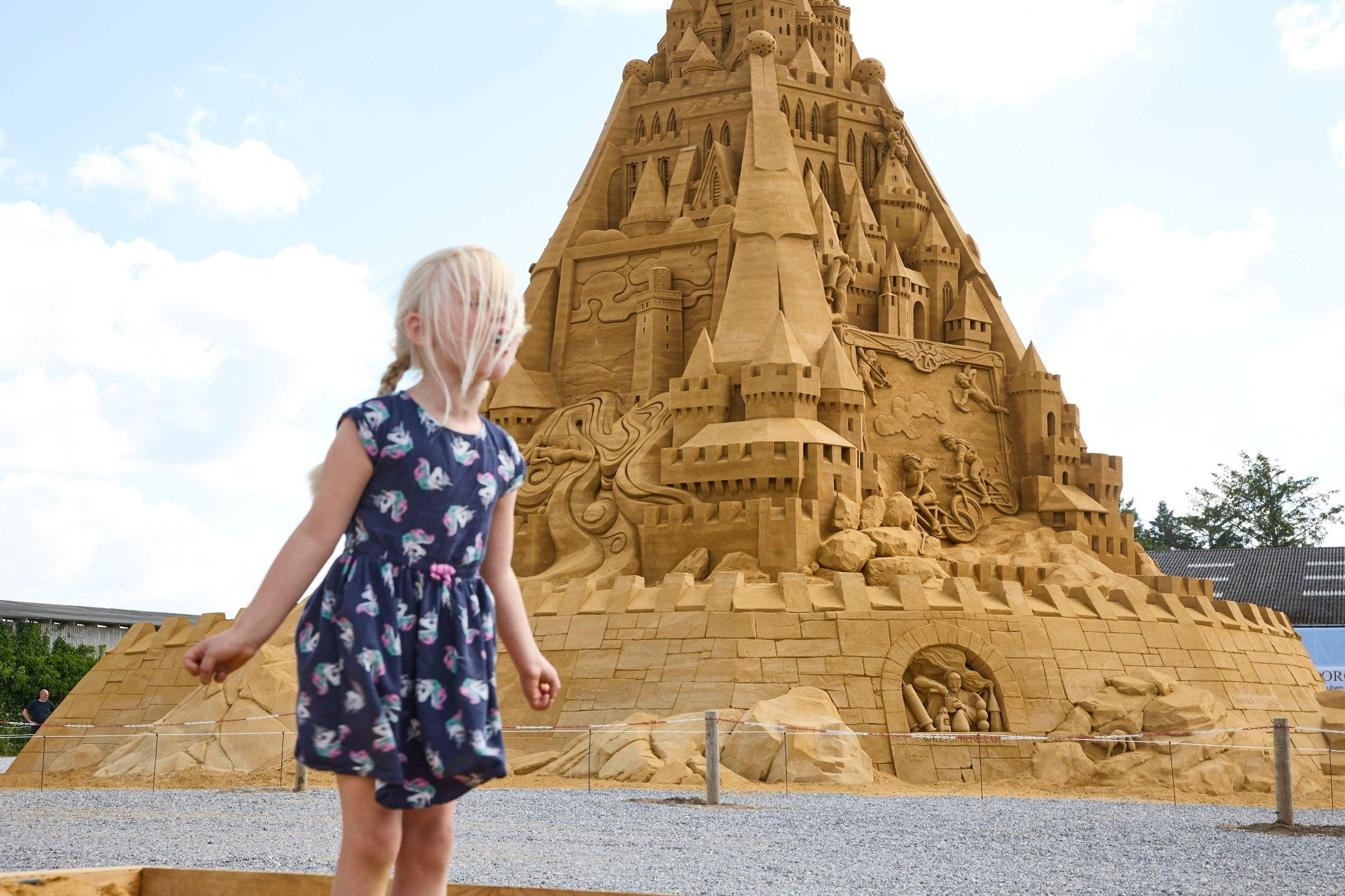 A girl plays in front of the world's tallest sand sculpture, under construction in Blokhus, Denmark, July 7, 2021. (AFP Photo)