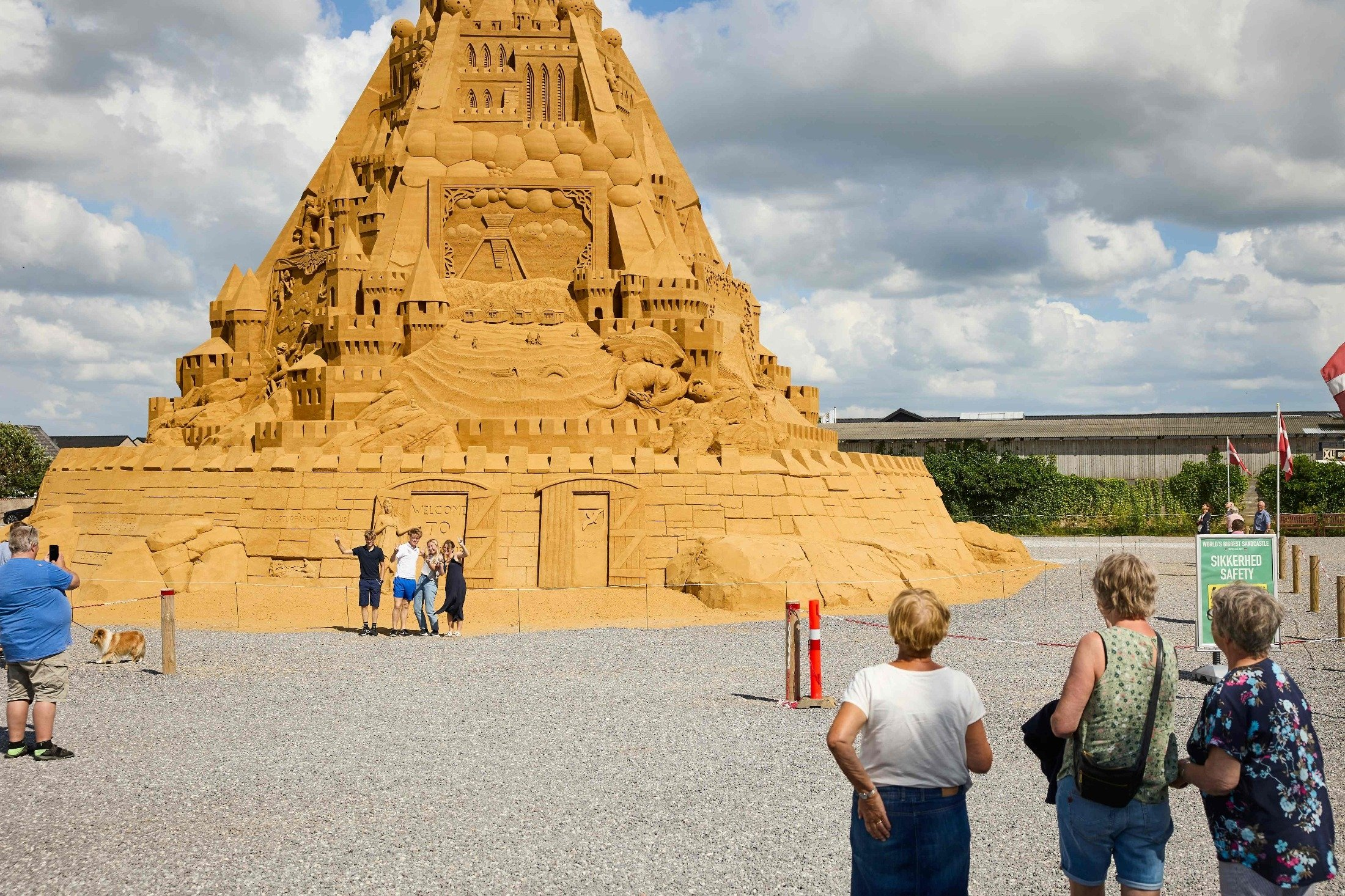 People pose for photos by the world's tallest sand sculpture, under construction in Blokhus, Denmark, July 7, 2021. (AFP Photo)