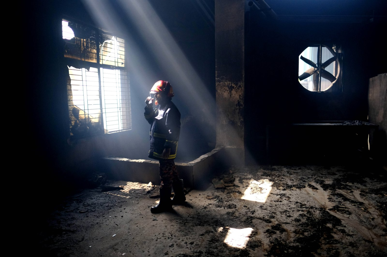 A firefighter communicates with his colleagues on a walkie-talkie inside the burnt food and beverage factory in Rupganj, outside Dhaka, Bangladesh, July 9, 2021. (AP Photo)