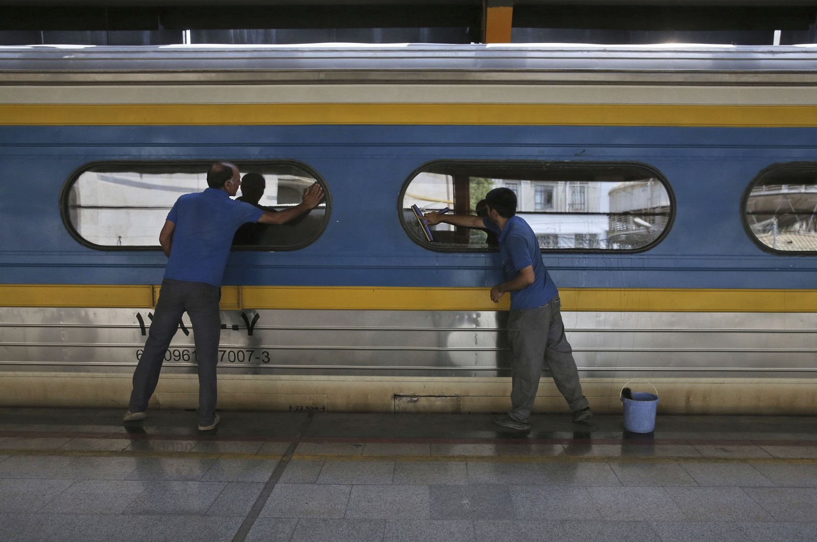 Two workers clean windows of a train's car at Tehran's central station, Tehran, Iran. July 10, 2017. (AP Photo/Vahid Salemi)
