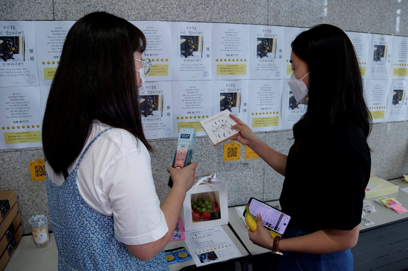 Women take a look at items at a feces currency market at Ulsan National Institute of Science and Technology (UNIST) in Ulsan, South Korea, July 6, 2021. (Reuters Photo)