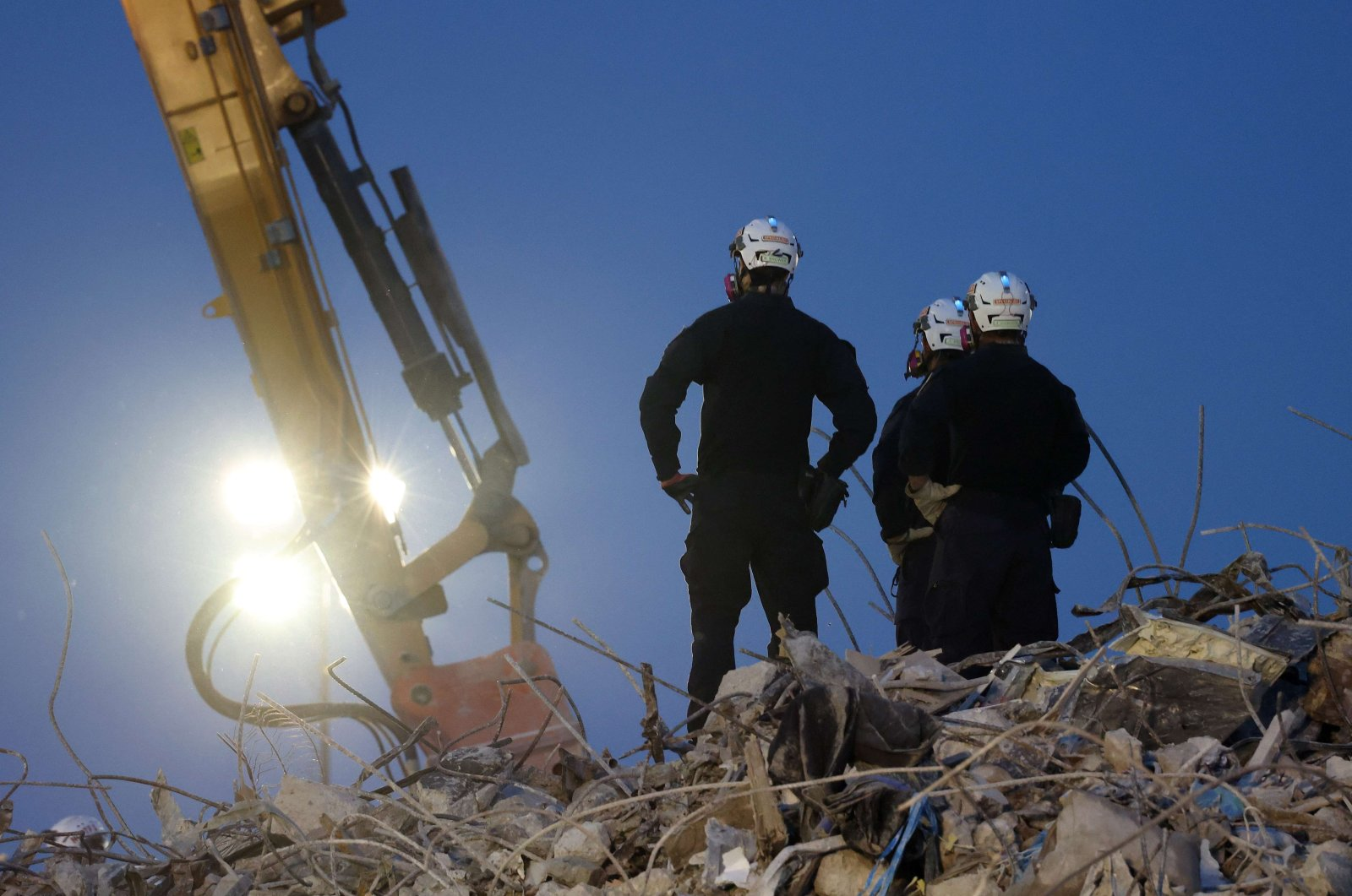 Search and rescue workers oversee an excavator dig through the rubble of the collapsed 12-story Champlain Towers South condo building on July 9, 2021 in Surfside, Florida. (Anna Moneymaker/Getty Images/AFP)