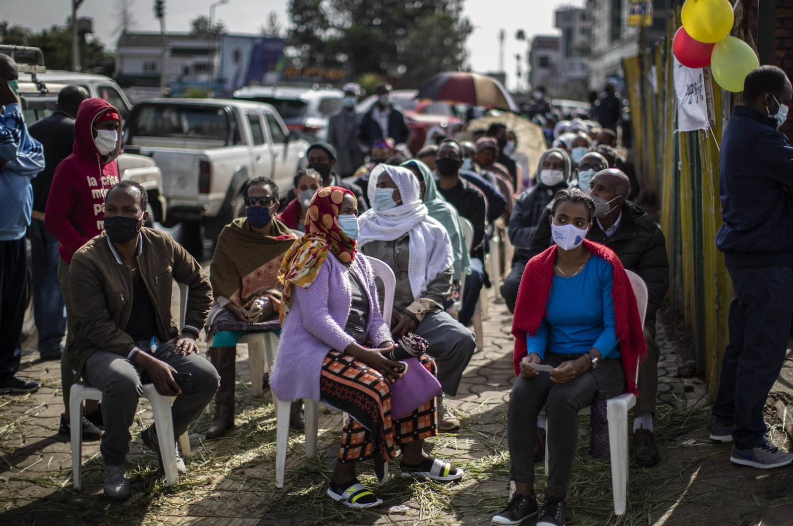 Ethiopians queue on chairs in the street as they wait to cast their votes in the general election at a polling center in the capital Addis Ababa, Ethiopia, Monday, June 21, 2021. (AP Photo)