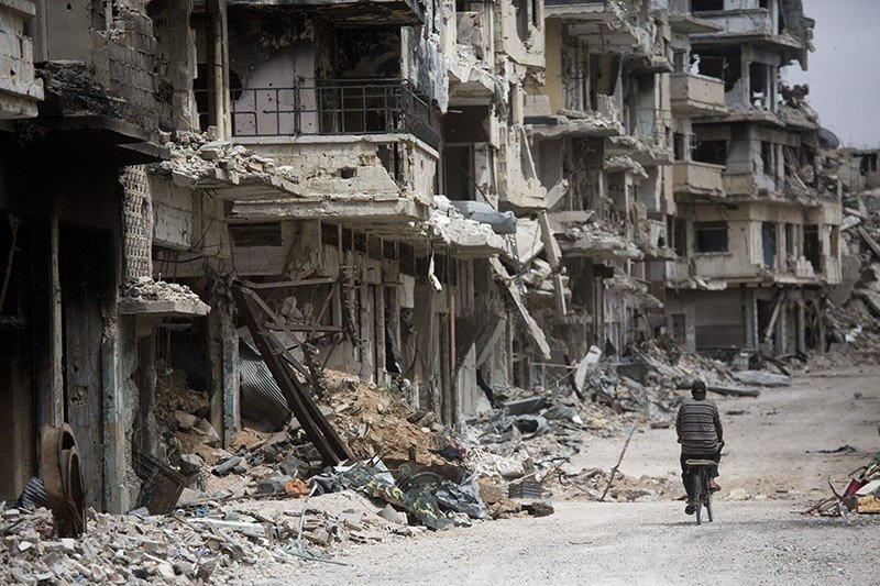 In this June 5, 2014 file photo, a man rides a bicycle through a devastated part of Homs, Syria. (AP Photo)