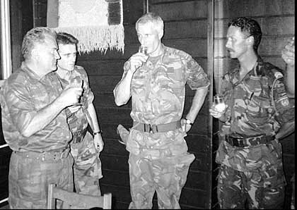 Bosnian Serb army Commander General Ratko Mladic, left, drinks toast with Dutch U.N Commander Tom Karremans, second right, while others unidentified look on in vilage of Potocari, some 5 kilometers (3 miles) north of Srebrenica, July 12,1995. (AP Photo)