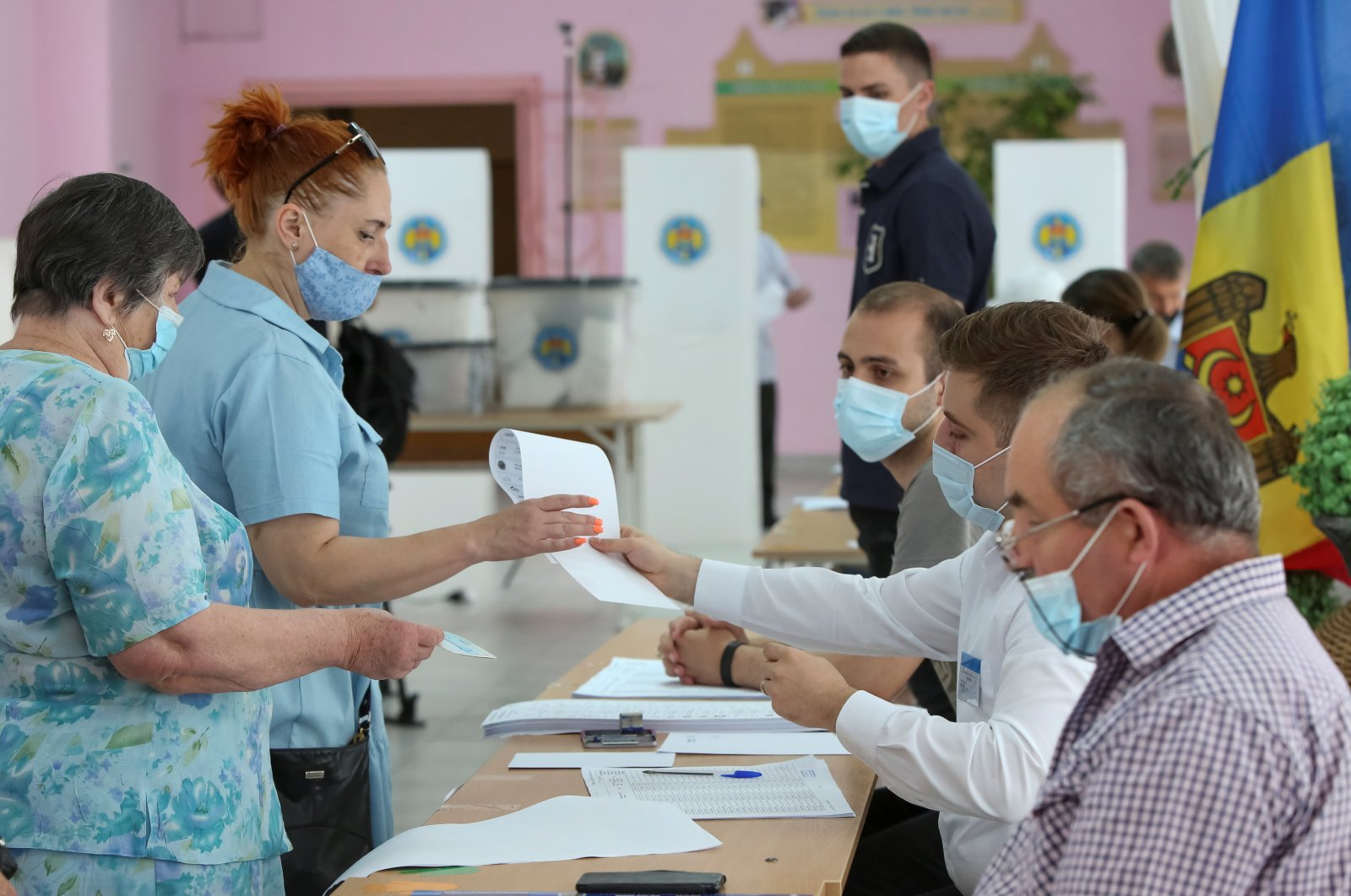 People queue to receive ballots during a vote at a snap parliamentary election, in Chisinau, Moldova July 11, 2021. (Reuters Photo)