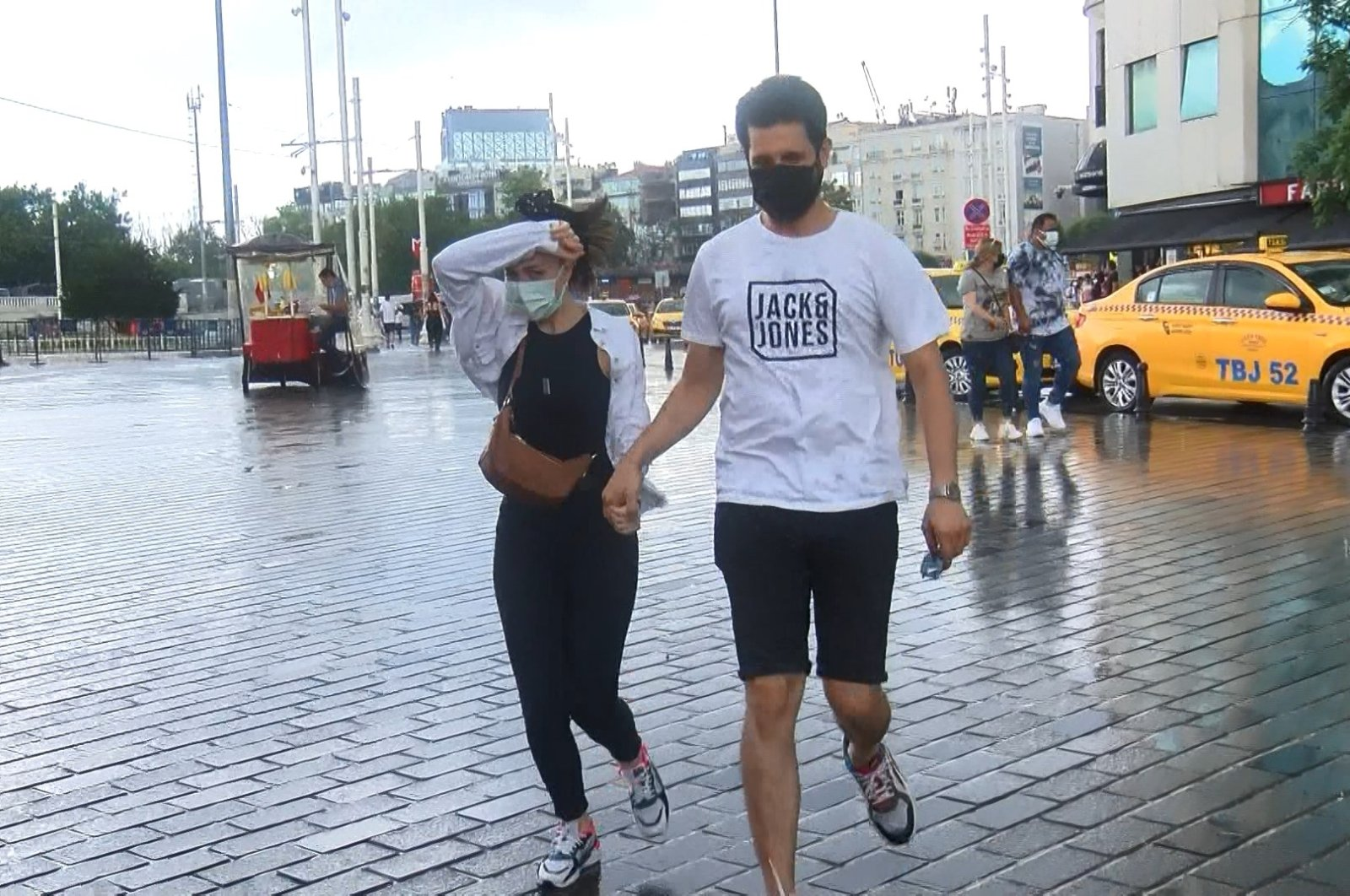 A couple wearing masks walks around Istanbul's famous Taksim Square in the rain, Istanbul, Turkey, July 4, 2021. (DHA Photo)