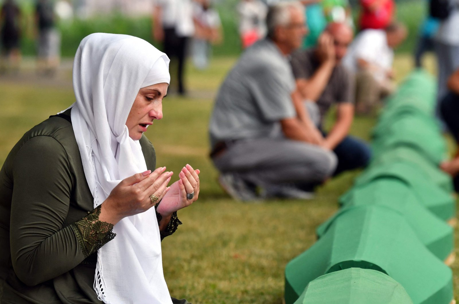 A Muslim Bosnian woman, a survivor of the Srebrenica 1995 massacre, prays as she mourns near the casket of her relative, at the memorial cemetery in the village of Potocari, near the eastern Bosnian town of Srebrenica, on July 10, 2021. (AFP Photo)