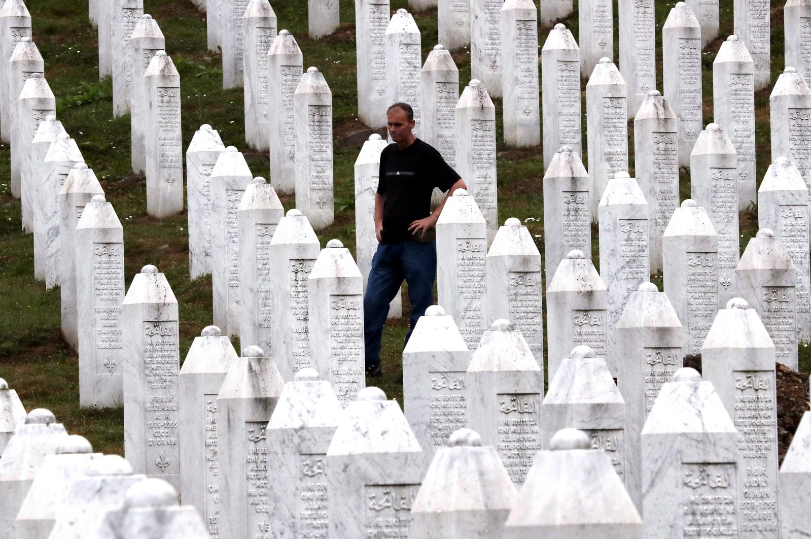 A Bosnian Muslim man mourns while touching a gravestone during a funeral ceremony for nineteen newly-identified Bosnian Muslim victims, at the Potocari Memorial Center and Cemetery, in Srebrenica, Bosnia-Herzegovina, July 11, 2021. (EPA Photo)
