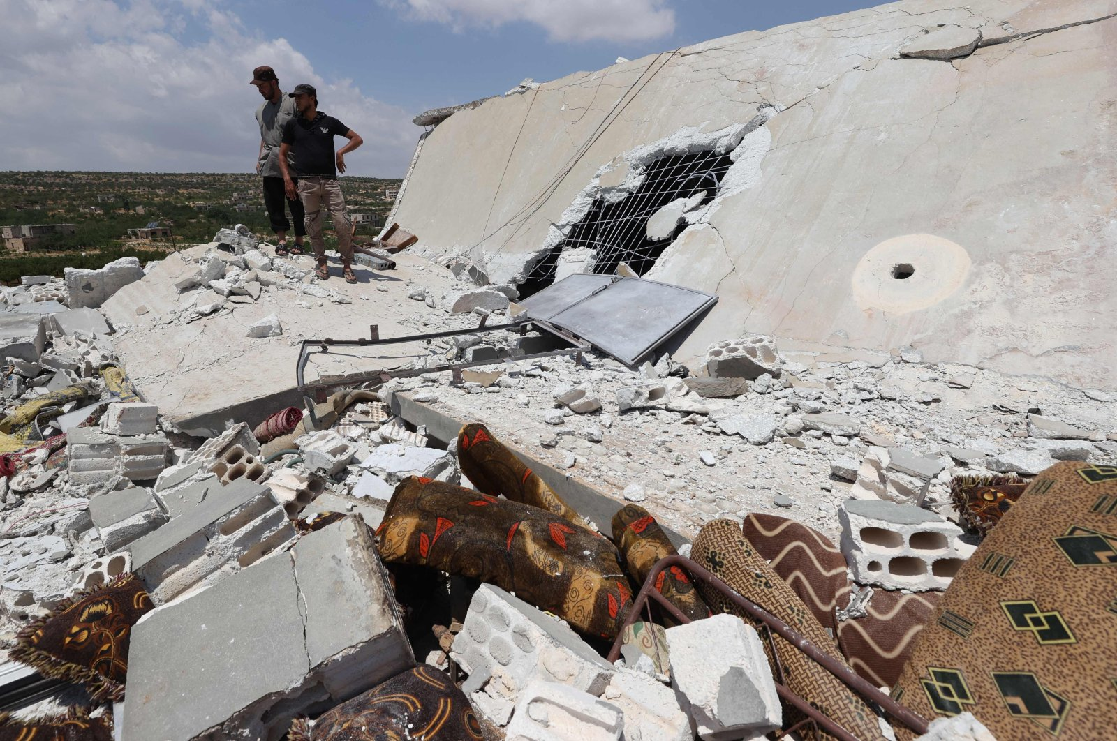 People inspect a damaged house destroyed by a Russian missile attack in the Jabal al-Zawiya region in the south of Syria's rebel-held Idlib province, July 4, 2021. (Photo by Omar Haj Kadour/AFP)