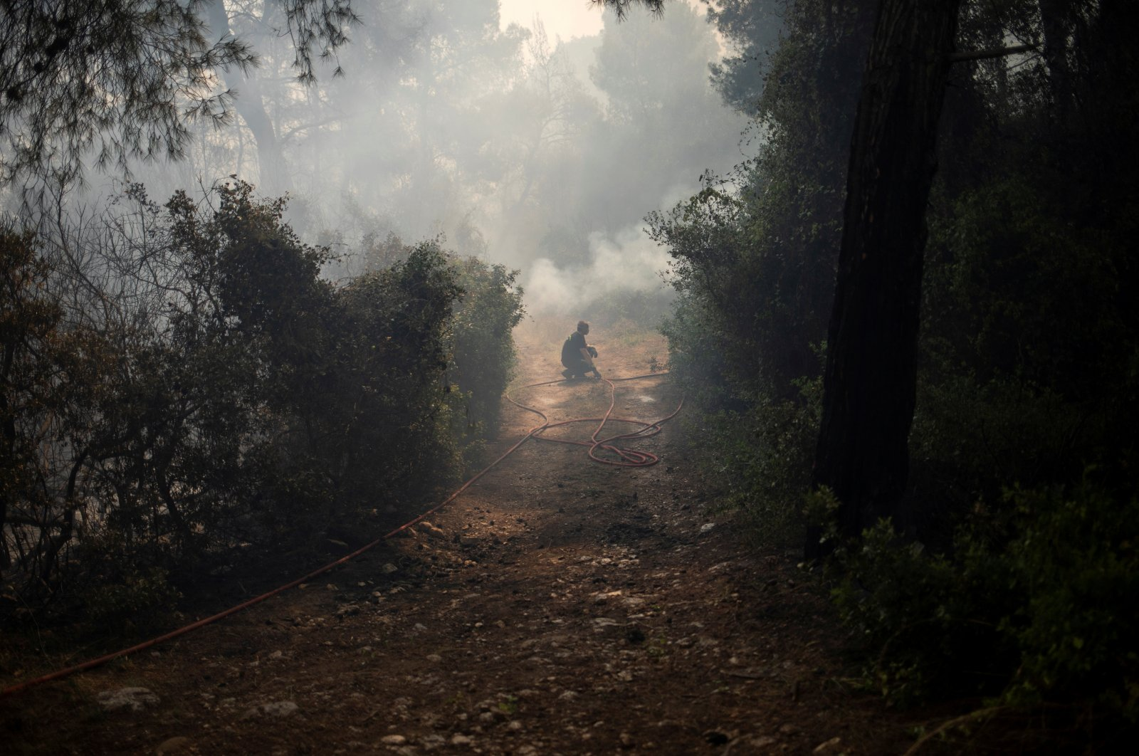 A firefighter pauses as he tries to extinguish a fire burning in the village of Mazi, near Corinth, Greece, May 20, 2021. (Reuters Photo)