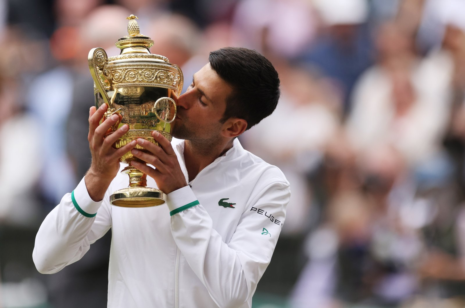 Serbia's Novak Djokovic celebrates with the trophy after winning his final match against Italy's Matteo Berrettini, All England Lawn Tennis and Croquet Club, London, U.K., July 11, 2021. (Reuters Photo)