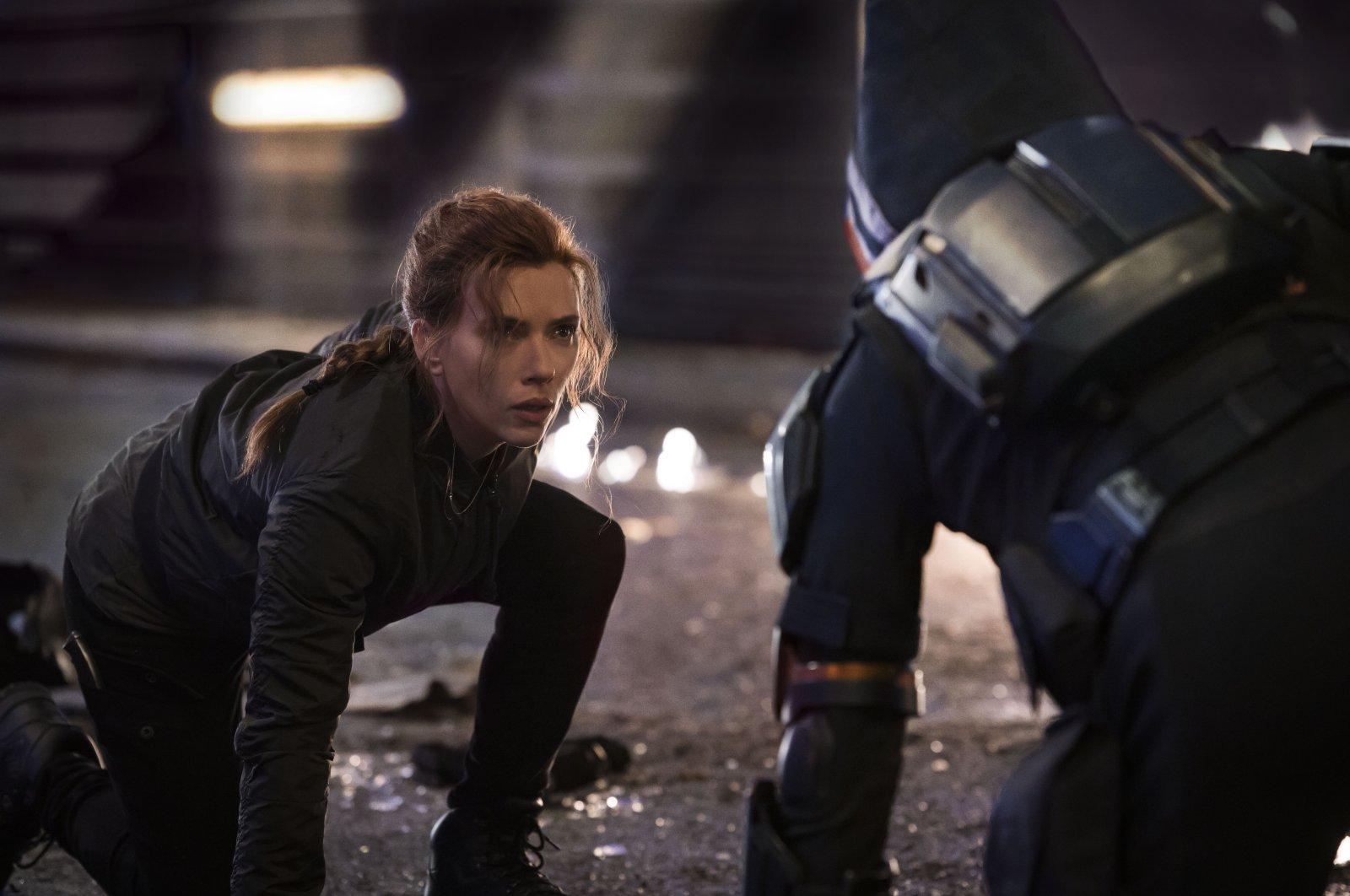 "Scarlett Johansson kneels duringan action scene in the film ""Black Widow."" (Disney via AP)"