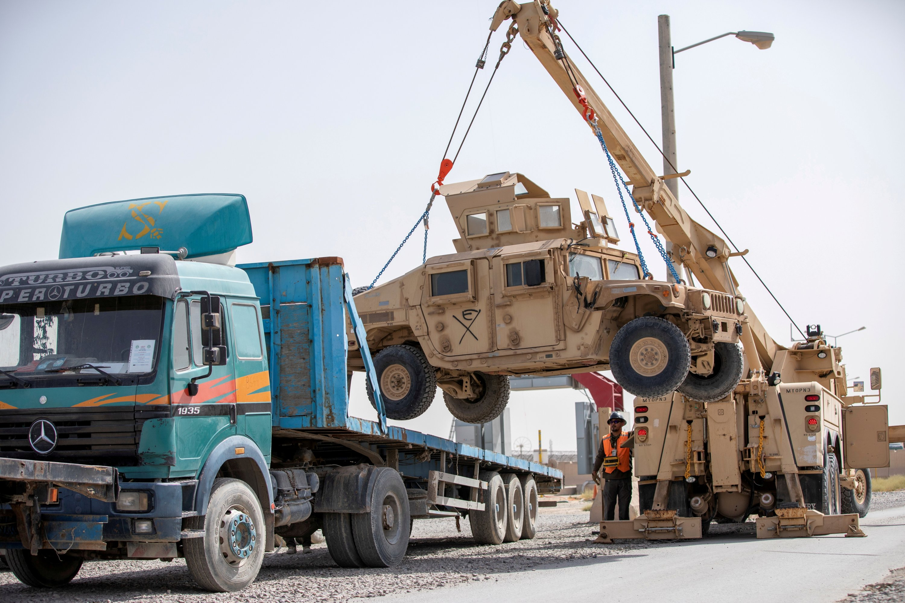 U.S. Army soldiers and contractors load High Mobility Multi-purpose Wheeled Vehicles, HUMVs, to be sent for transport as U.S. forces prepare for withdrawal, in Kandahar, Afghanistan, July 13, 2020. (U.S. Army/Sgt. Jeffery J. Harris/Handout via REUTERS)