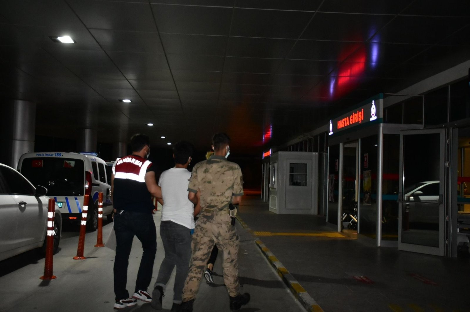 Gendarmerie officers escort a suspect to the hospital for medical checks, in Izmir, western Turkey, July 12, 2021. (DHA PHOTO)