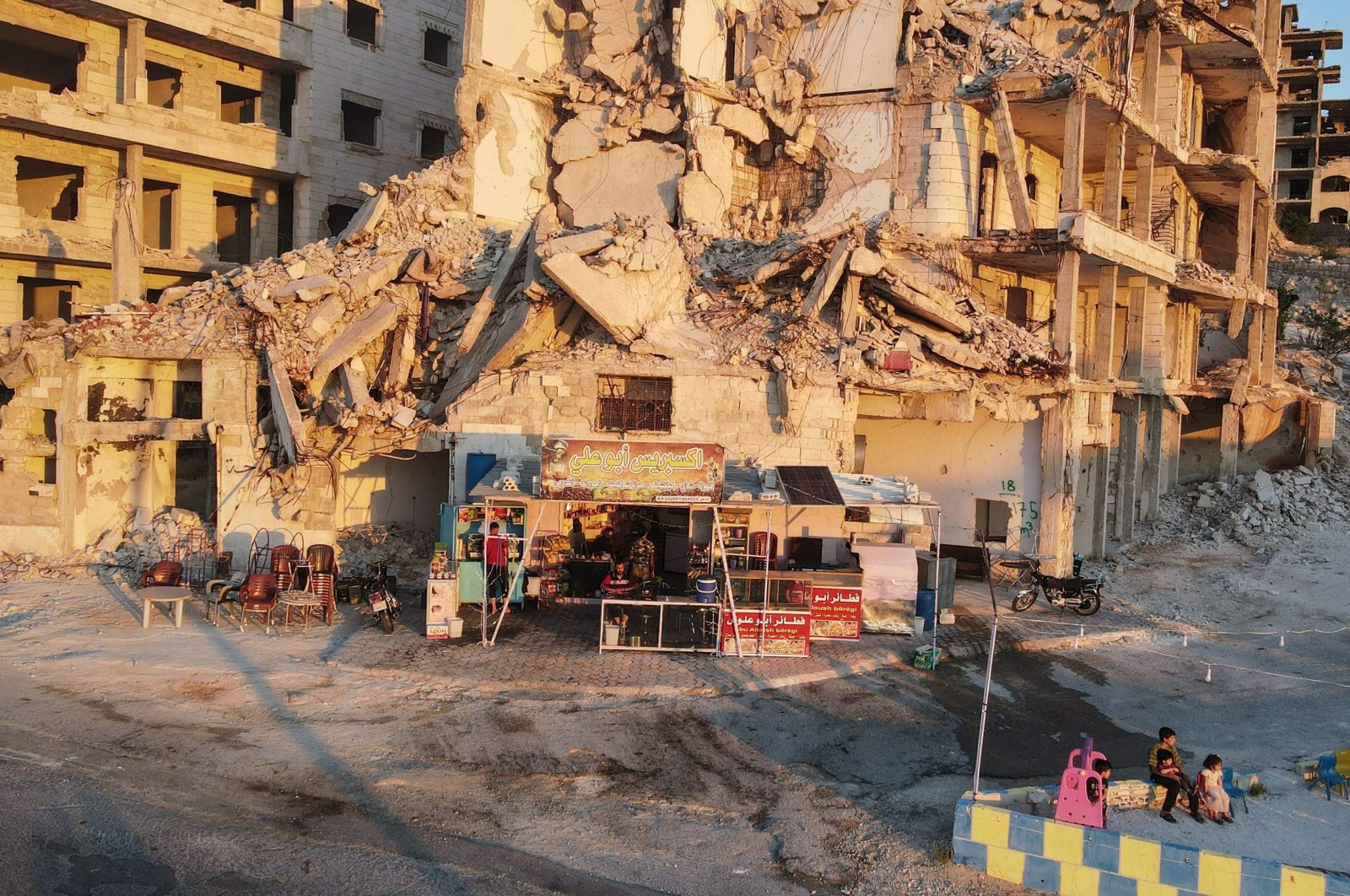 Children gather in the playground in front of Abu Ali's cafe, set up on the ground floor of a building heavily damaged during the civil war, in the Jabal al-Arbain hiltop residential area, in the Syrian town of Ariha in the opposition-held northwestern Syrian Idlib province, July 11, 2021. (AFP Photo)