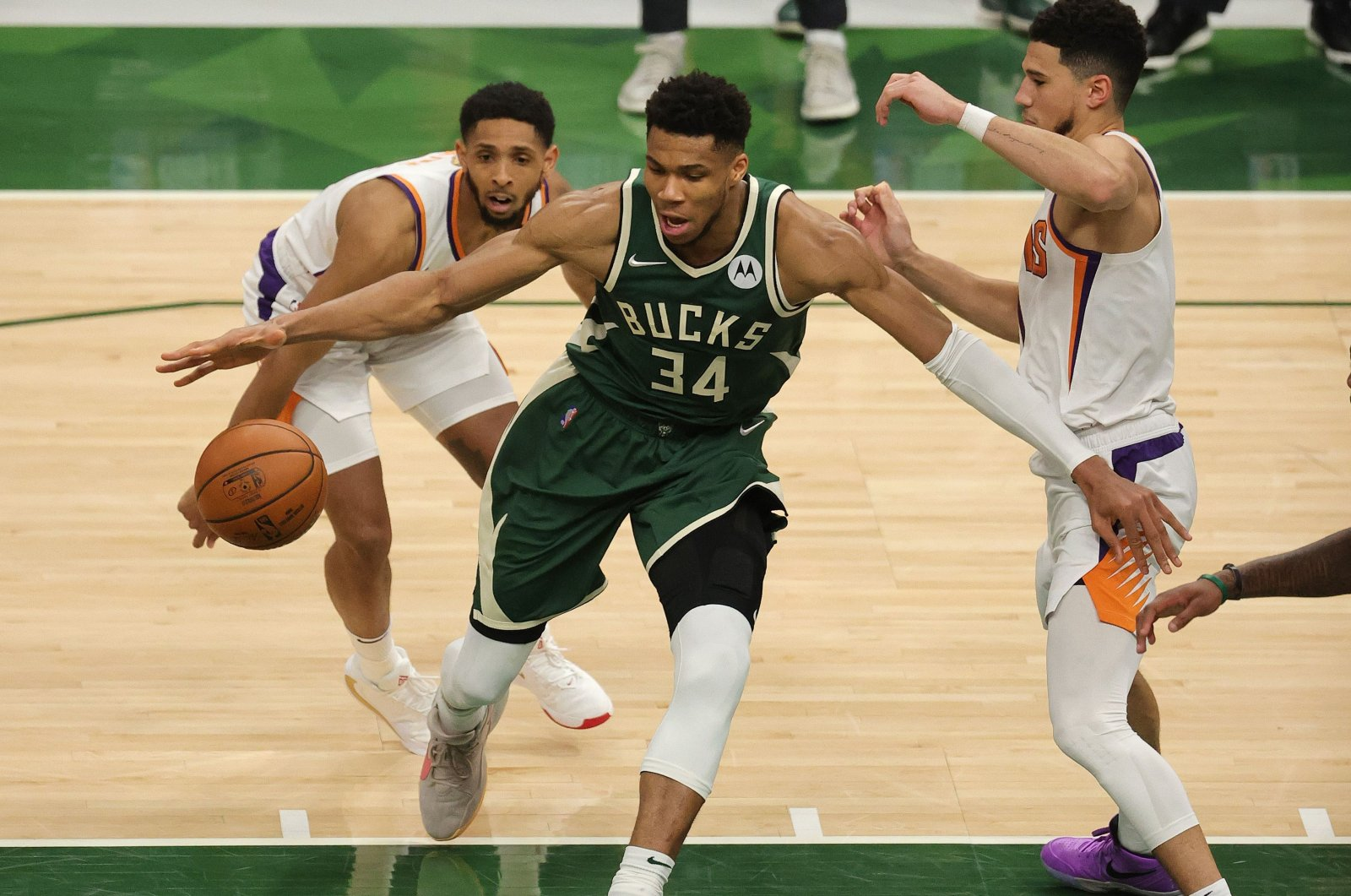 Milwaukee Bucks' Giannis Antetokounmpo (C) drives into the lane as Phoenix Suns' Devin Booker (R) defends during the NBA Finals Game 3 at Fiserv Forum, Milwaukee, Wisconsin, U.S., July 11, 2021. (AFP Photo)