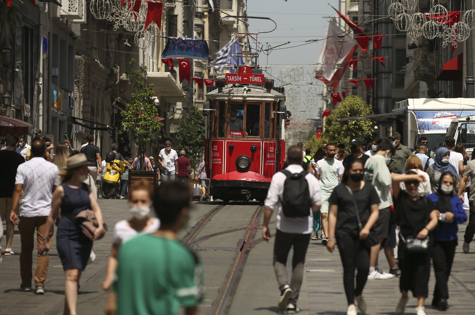 People walk on Istiklal Avenue, the main shopping street in Istanbul, Turkey, July 1, 2021. (AP Photo)