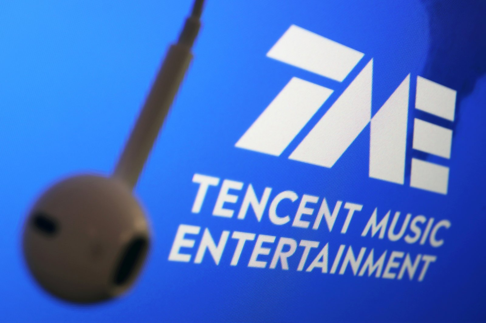 The logo of China's Tencent Music Entertainment Group is seen next to an earphone in this illustration picture taken March 22, 2021. (Reuters Photo)