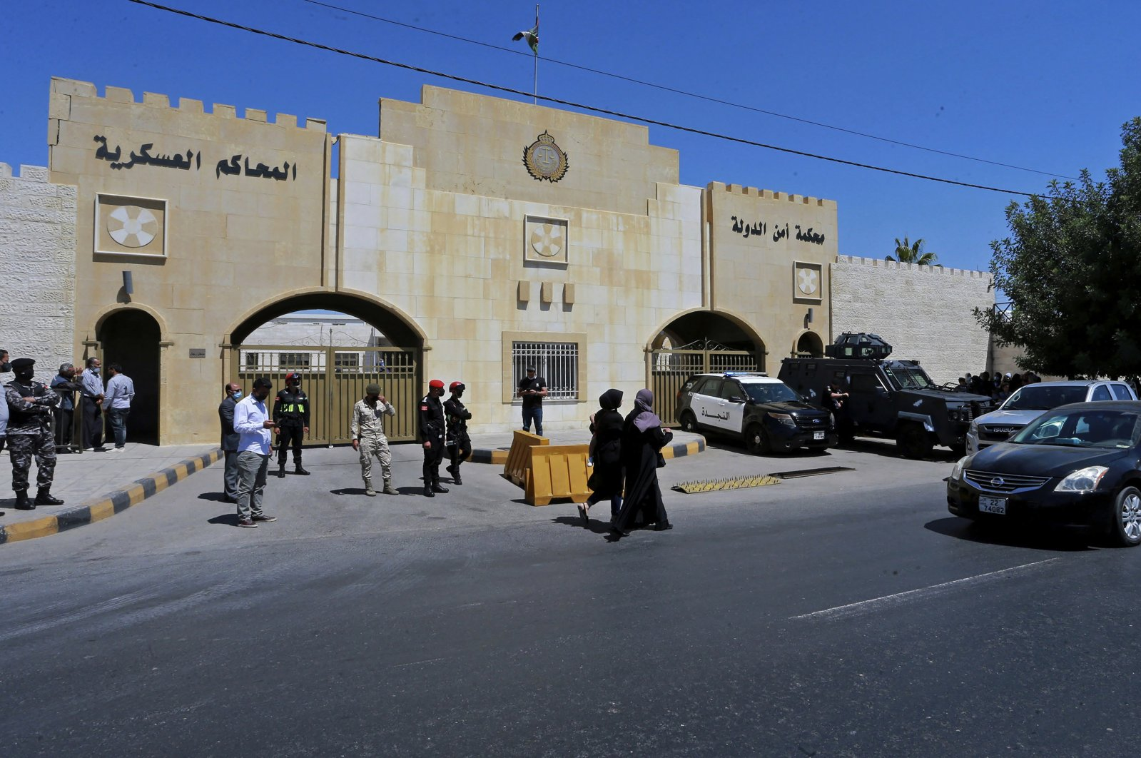 Security forces stand outside the state security court where the trial of Bassem Awadallah, a former royal adviser, and Sharif Hassan bin Zaid, a distant cousin of the king, is taking place, in Amman, Jordan, June 21, 2021. (AP Photo)