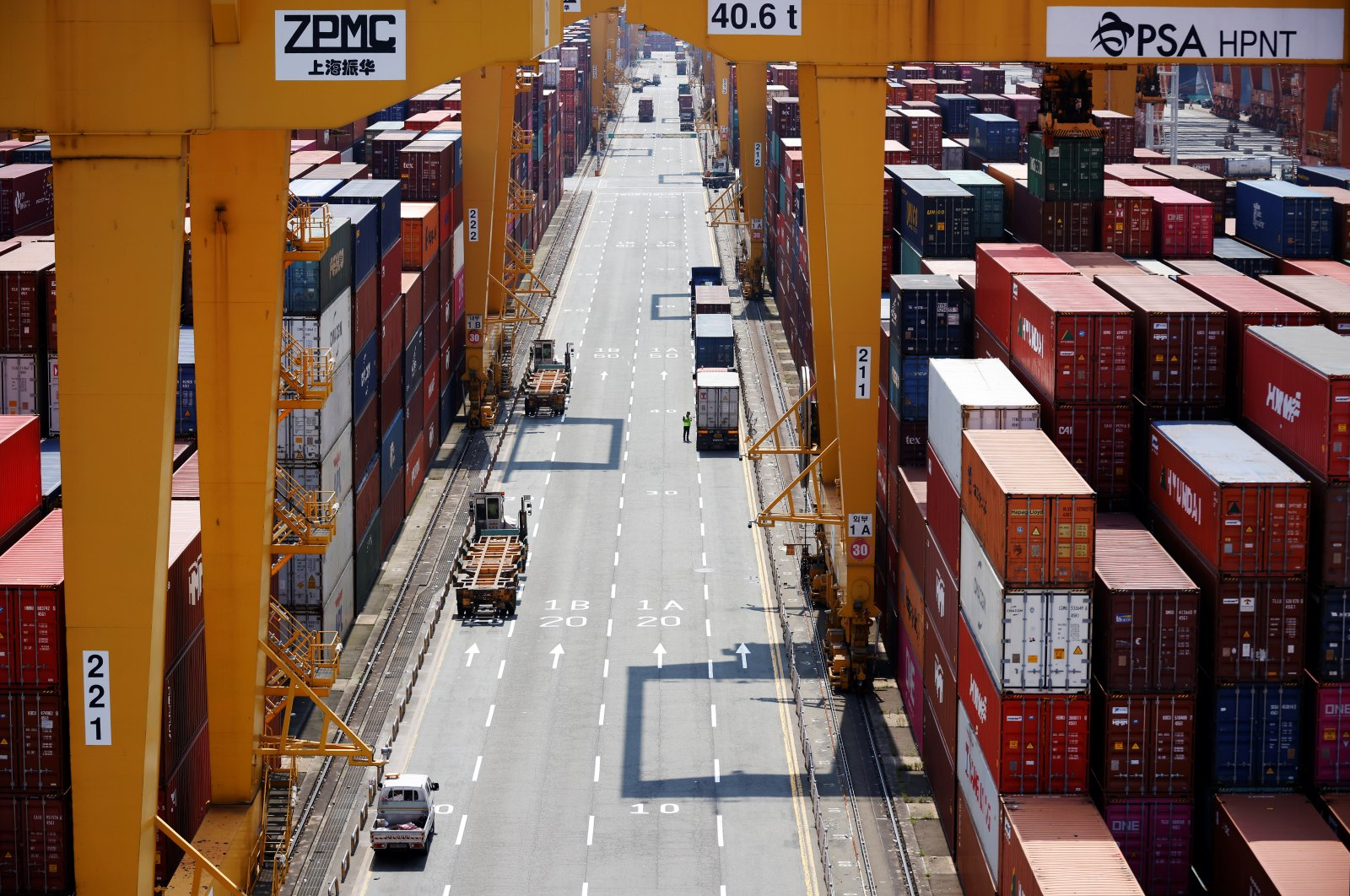 A truck driver stands next to his truck as he gets ready to transport a shipping container at Pusan Newport Terminal in Busan, South Korea, July 1, 2021. (Reuters Photo)