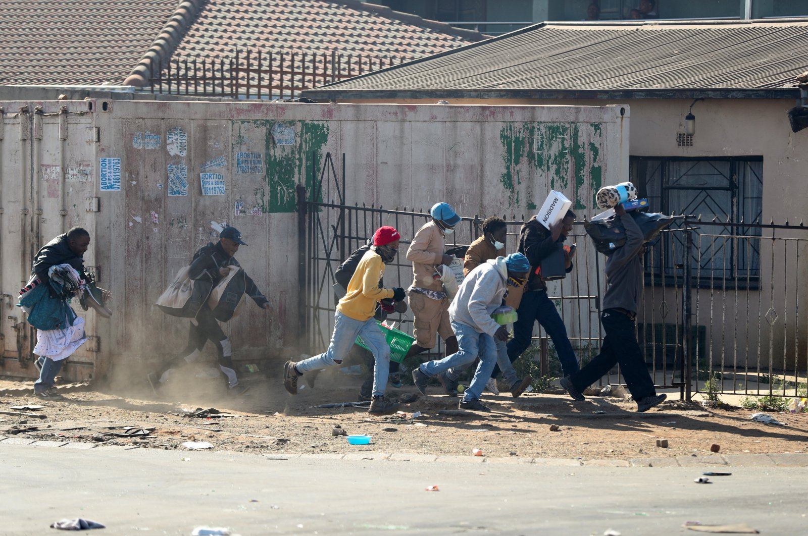 People run with looted goods, as protests continue following imprisonment of former South Africa President Jacob Zuma, in Katlehong, South Africa, July 12, 2021. (Reuters Photo)