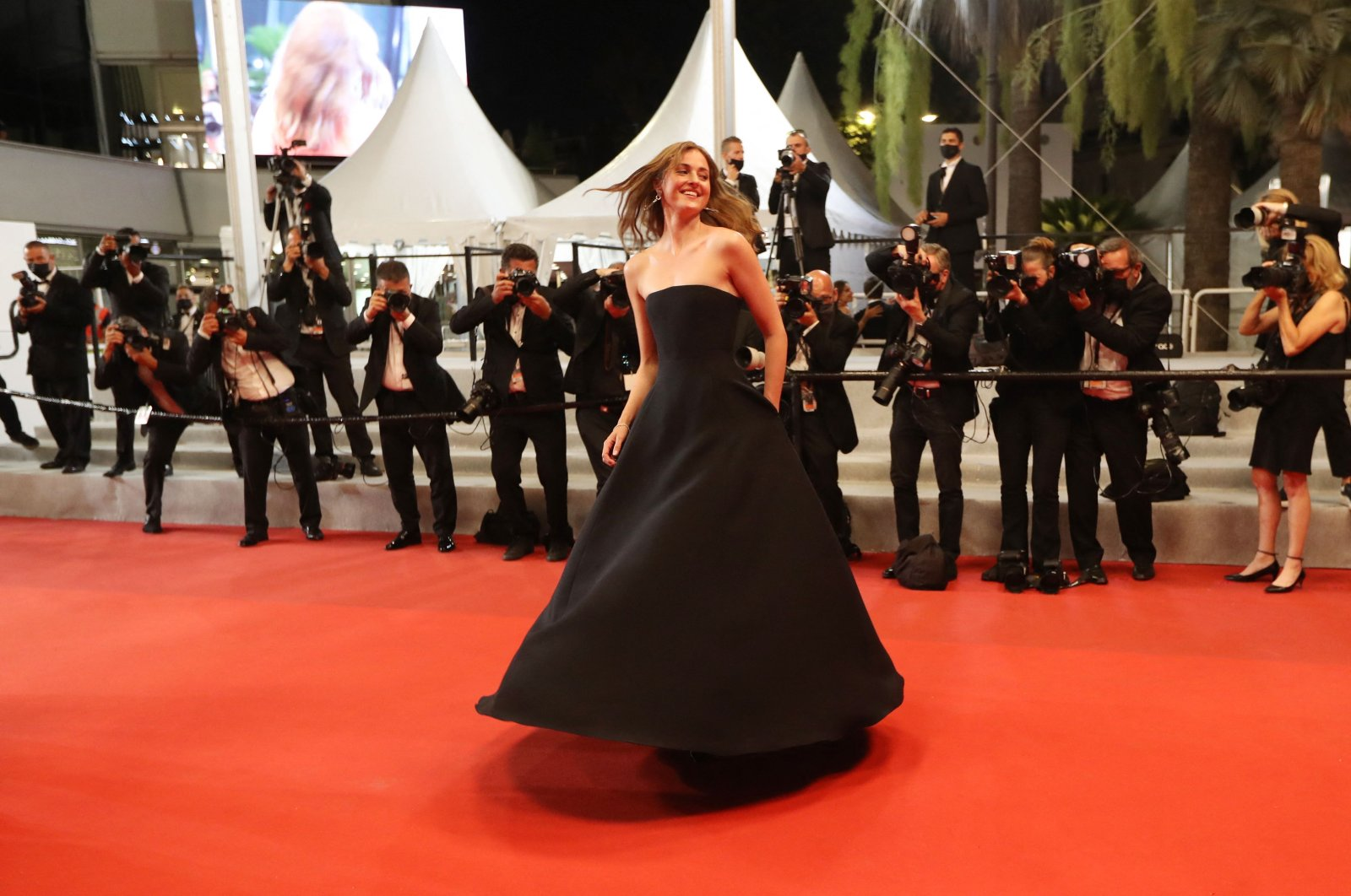 """Norwegian actress Renate Reinsve dances as she arrives for the screening of the film """"Verdens Verste Menneske"""" (The Worst Person In The World) at the 74th Cannes Film Festival in Cannes, France, July 8, 2021. (AFP Photo)"""