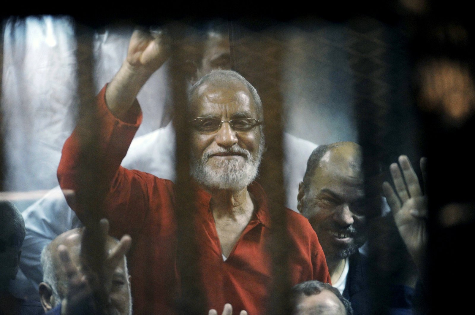 Muslim Brotherhood spiritual leader Mohammed Badie waves from the defendants cage in a makeshift courtroom at the national police academy, in eastern Cairo, Egypt, May 16, 2015. (AP Photo)