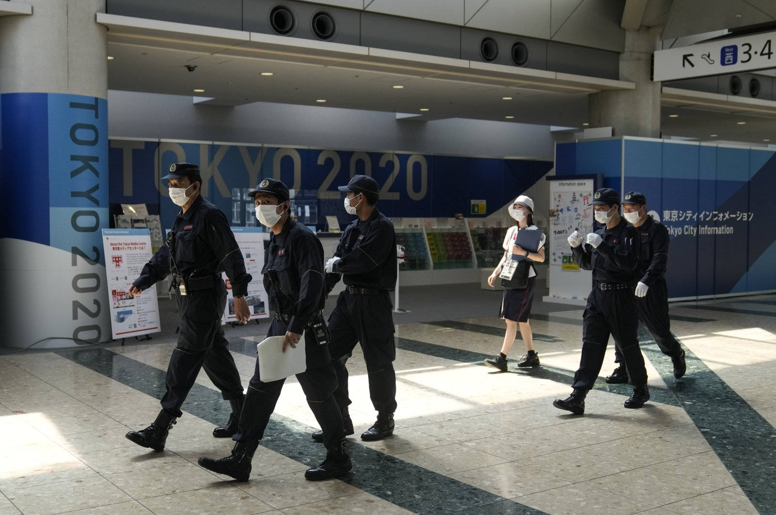 Police walk past the Tokyo 2020 banners as they prepare for a security check at the main press center of the 2020 Summer Olympics, in Tokyo, Japan, July 12, 2021. (AP Photo)