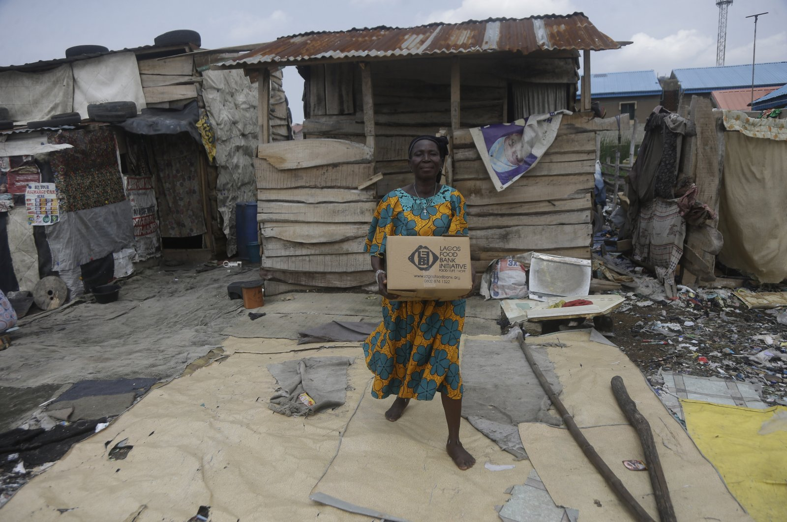 A resident of the Oworonshoki Slum carries a box of food distributed by the Lagos Food Bank Initiative, in Lagos, Nigeria, July 10, 2021. (AP Photo)