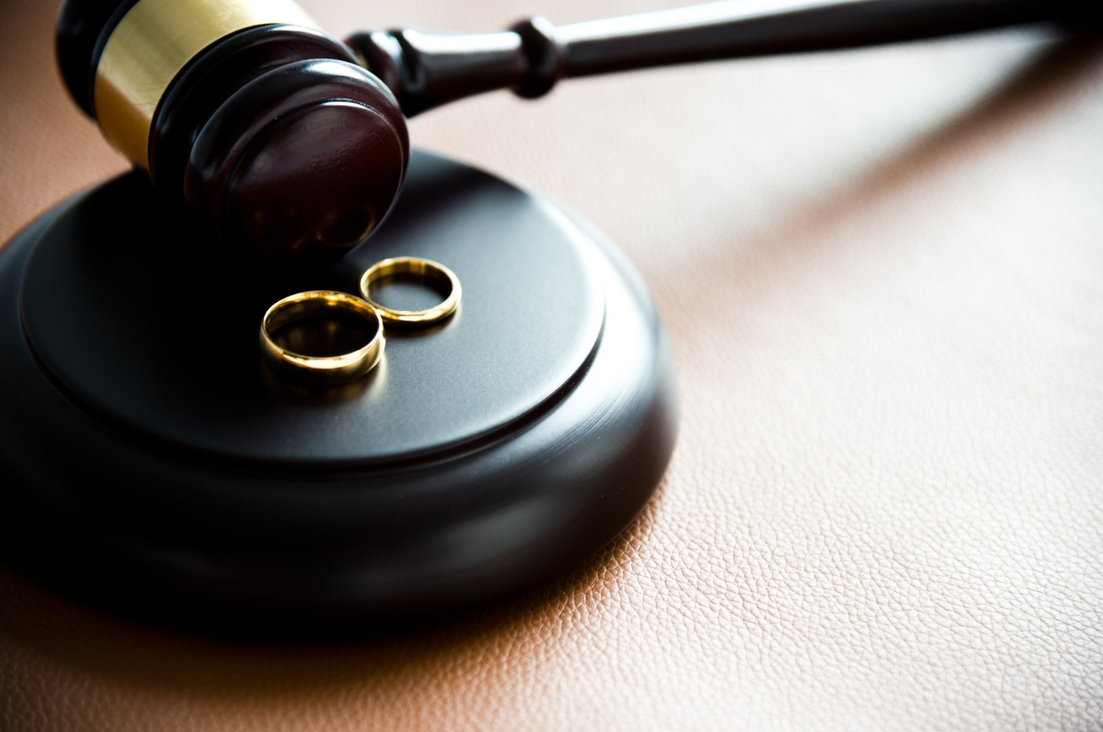 Two wedding rings rest near a judge's gavel. (Getty Photo)