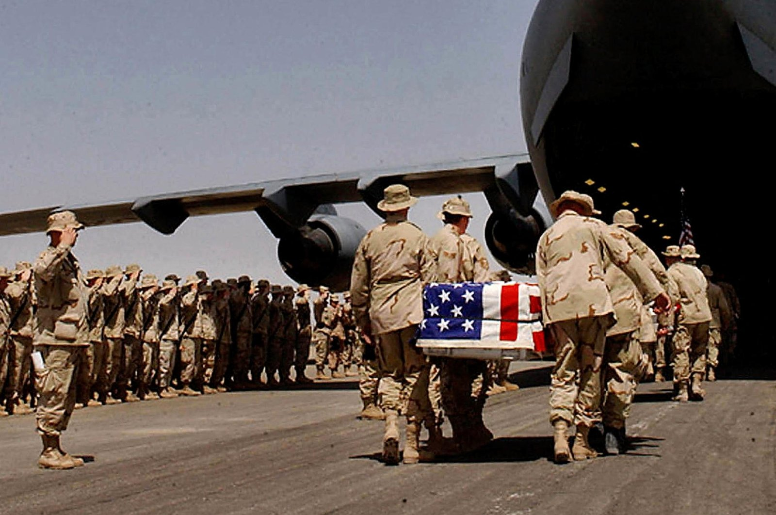 U.S. soldiers carry the coffins of their colleagues draped in national flags to a C-17 aircraft during a memorial ceremony held at Kandahar army base, Afghanistan, March 30, 2020. (AFP File Photo)