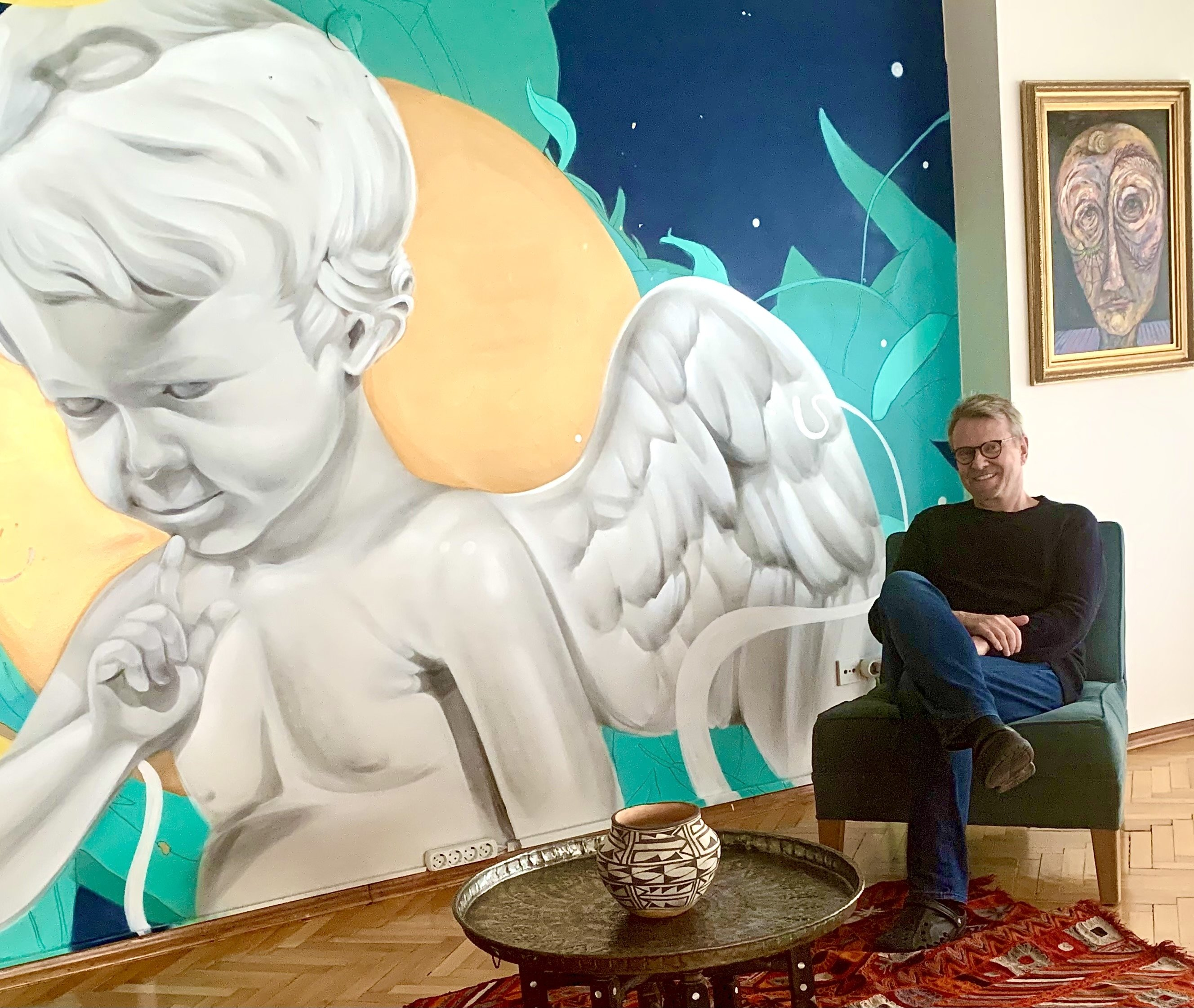Walter Meyer sits next to a mural. (Ferzan Altinsoy for Daily Sabah)