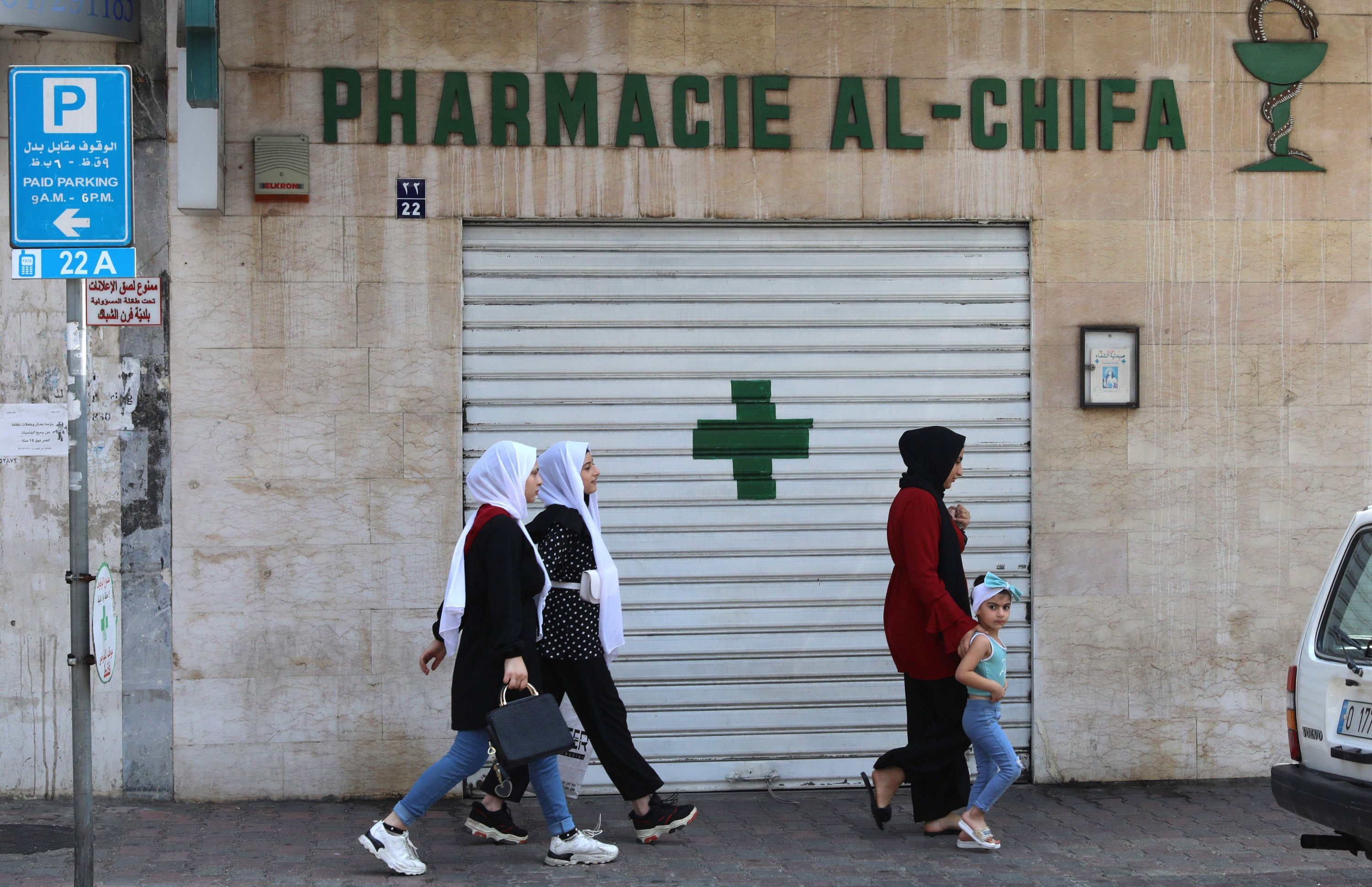 People walk in front of the shuttered door of a pharmacy, during a nationwide strike of pharmacies to protest against a severe shortage of medicine, Beirut, Lebanon, July 9, 2021. (AFP Photo)