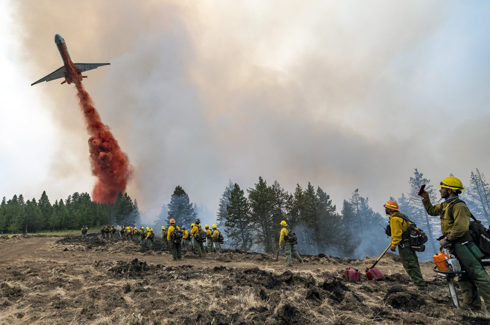 Wildland firefighters watch and take video with their cellphones as a plane drops fire retardant on Harlow Ridge above the Lick Creek Fire, southwest of Asotin, Washington, U.S., July 12, 2021. (Lewiston Tribune via AP)